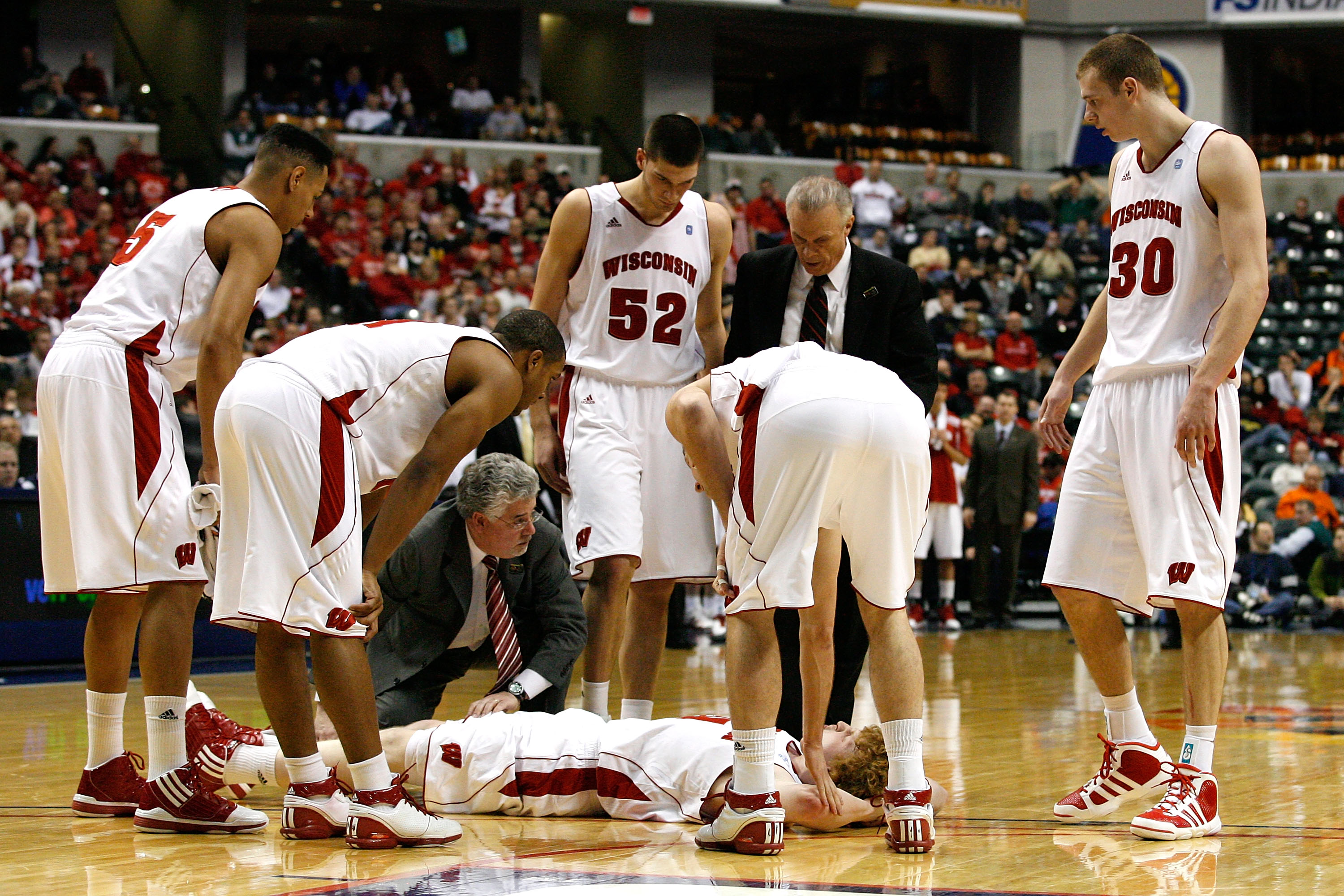 INDIANAPOLIS, IN - MARCH 11:  Mike Bruesewitz #31 of the Wisconsin Badgers is attended to by head coach Bo Ryan and the Badgers medical staff after he was hurt in the second half during the quarterfinals of the 2011 Big Ten Men's Basketball Tournament at