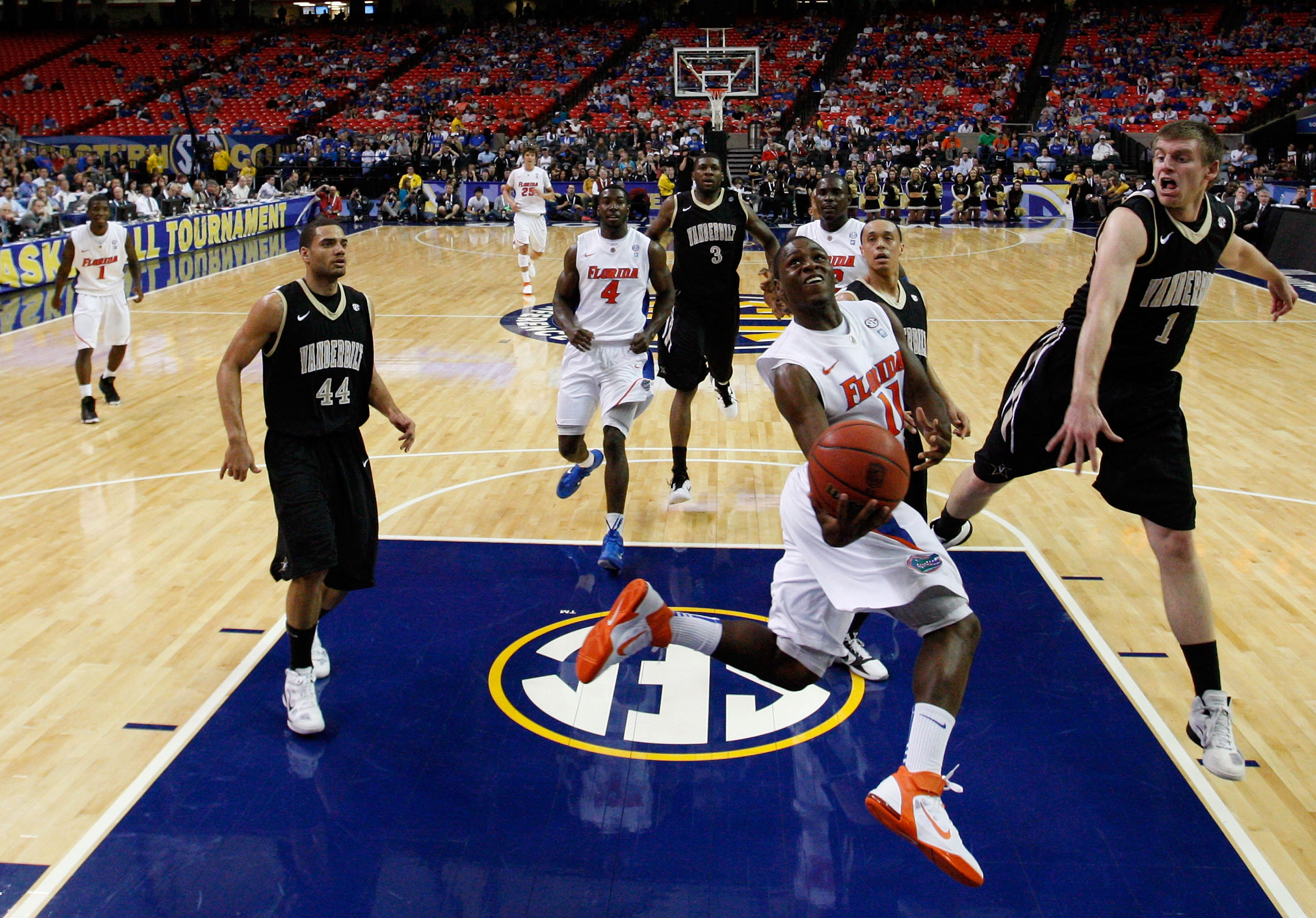 ATLANTA, GA - MARCH 12:  Erving Walker #11 of the Florida Gators shoots against Brad Tinsley #1 of the Vanderbilt Commodores during the semifinals of the SEC Men's Basketball Tournament at Georgia Dome on March 12, 2011 in Atlanta, Georgia.  (Photo by Kev