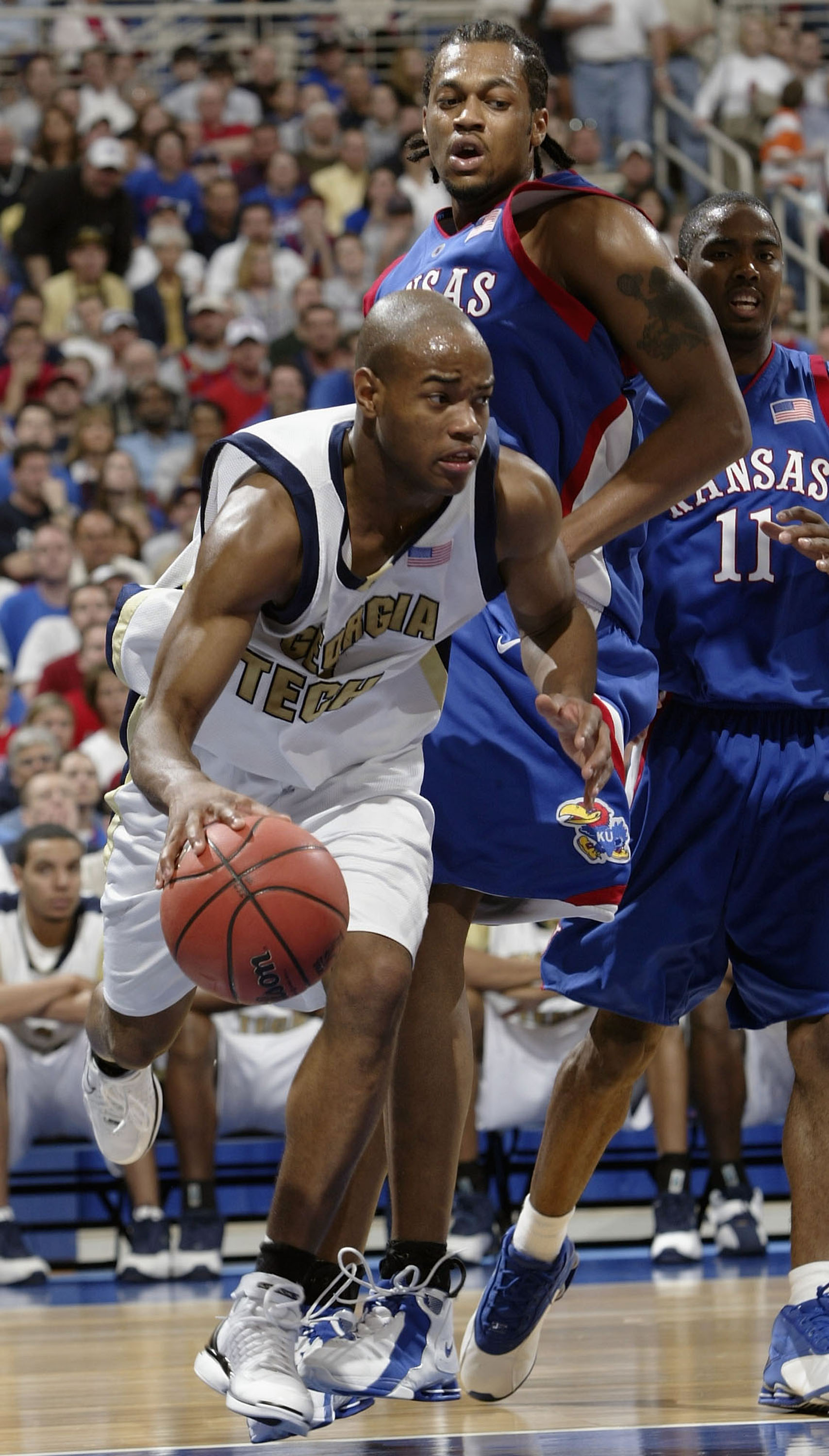 ST. LOUIS - MARCH 28: Jarrett Jack #3 of the Georgia Tech Yellow Jackets drives past Jeff Graves #42 of the Kansas Jayhawks during the fourth round game of the NCAA Division I Men's Basketball Tournament at the Edward Jones Dome on March 28, 2004 in St. L