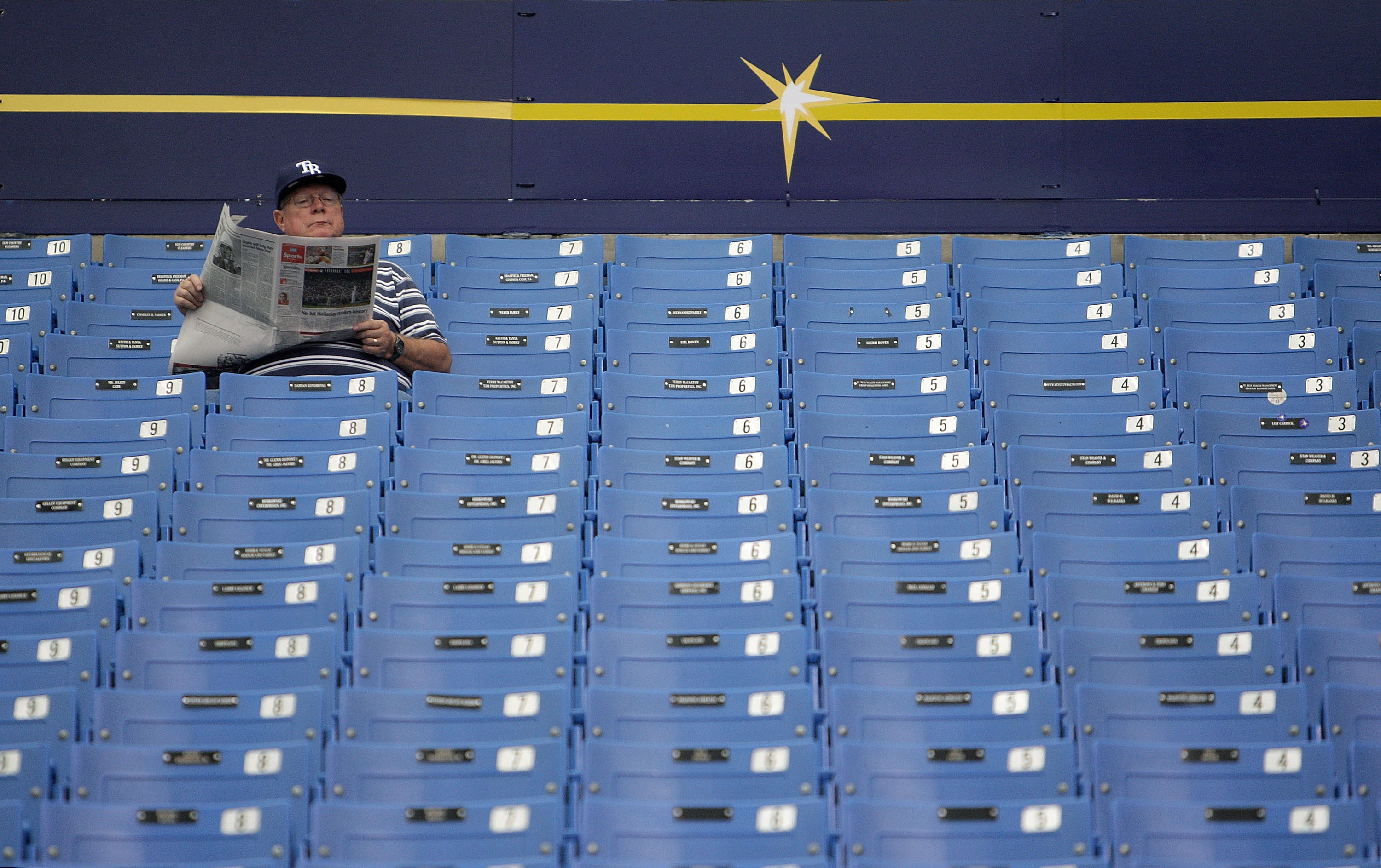 ST PETERSBURG, FL - OCTOBER 07:  A Tampa Bay Rays fan reads the paper before Game 2 of the ALDS between the Tampa Bay Rays and the Texas Rangers at Tropicana Field on October 7, 2010 in St. Petersburg, Florida.  (Photo by Mike Ehrmann/Getty Images)