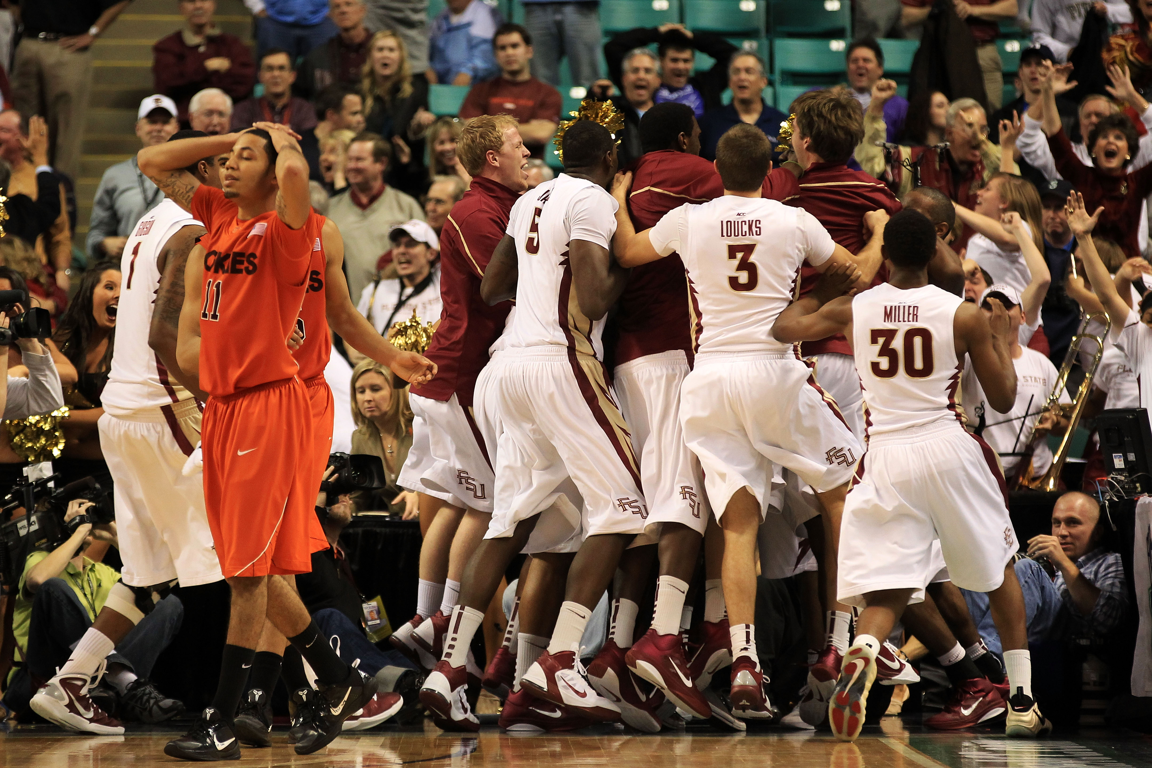 GREENSBORO, NC - MARCH 11:  Erick Green #11 of the Virginia Tech Hokies reacts to a shot at the buzzer by Derwin Kitchen #22 of the Florida State Seminoles as the Seminoles celebrate what would have been a victory for them during the quarterfinals of the