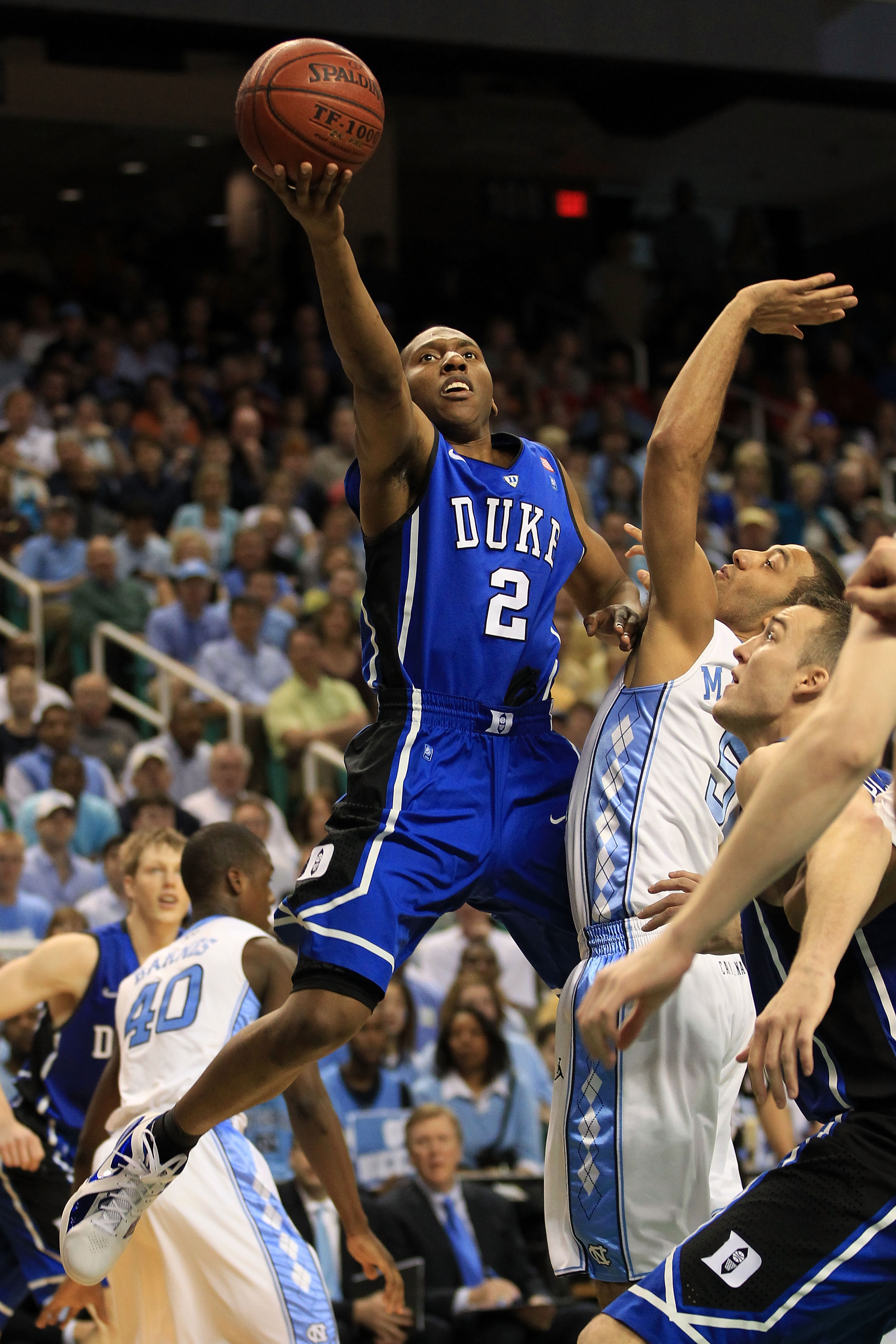 GREENSBORO, NC - MARCH 13:  Nolan Smith #2 of the Duke Blue Devils shoots against Kendall Marshall #5 of the North Carolina Tar Heels during the first half in the championship game of the 2011 ACC men's basketball tournament at the Greensboro Coliseum on