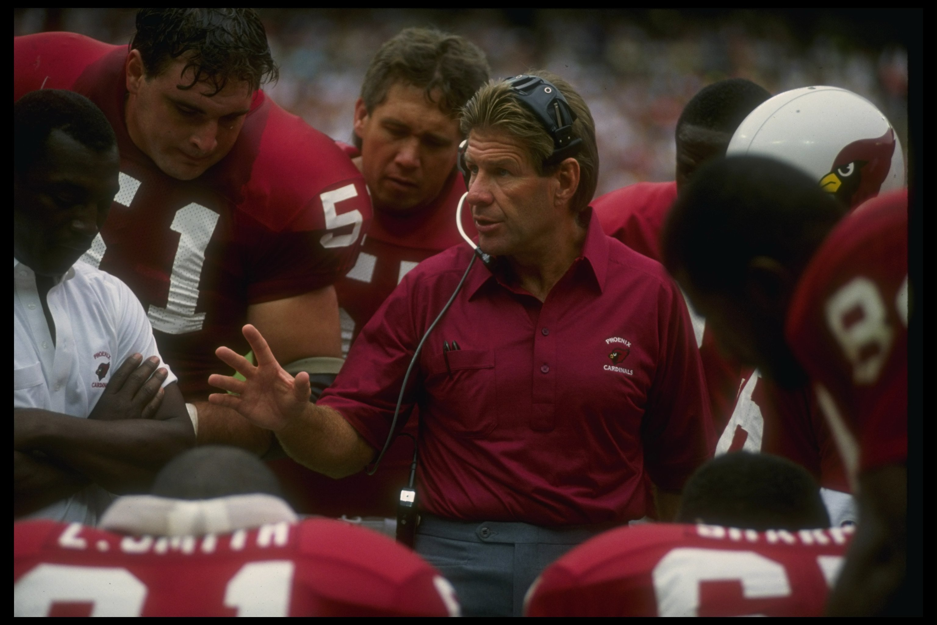 9 Sep 1990: Phoenix Cardinals head coach Joe Bugel confers with his team during a game against the Washington Redskins at Sun Devil Stadium in Tempe, Arizona. The Redskins won the game, 31-0.