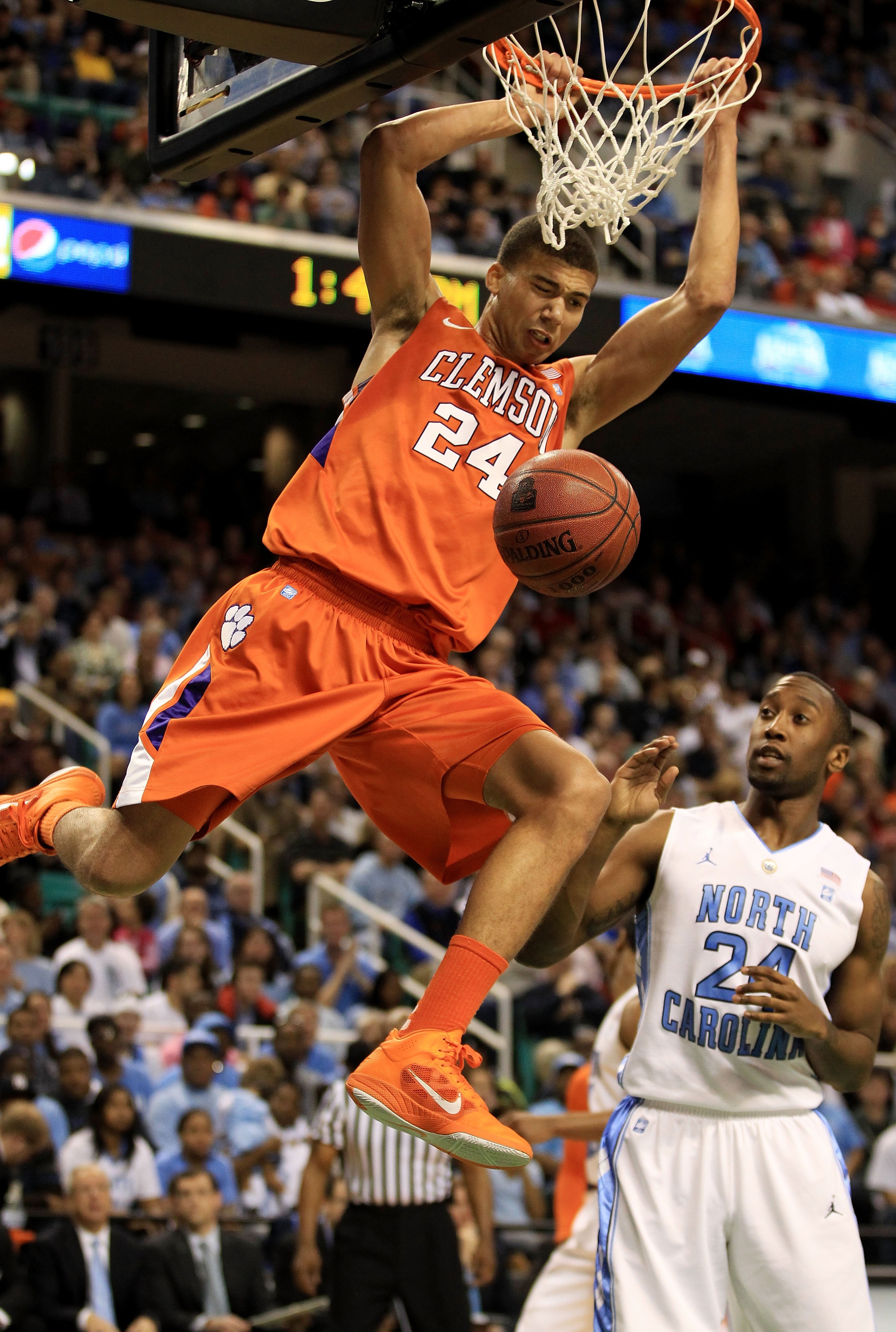 GREENSBORO, NC - MARCH 12:  Milton Jennings #24 of the Clemson Tigers shoots against Justin Watts #24 of the North Carolina Tar Heels during the first half in the semifinals of the 2011 ACC men's basketball tournament at the Greensboro Coliseum on March 1