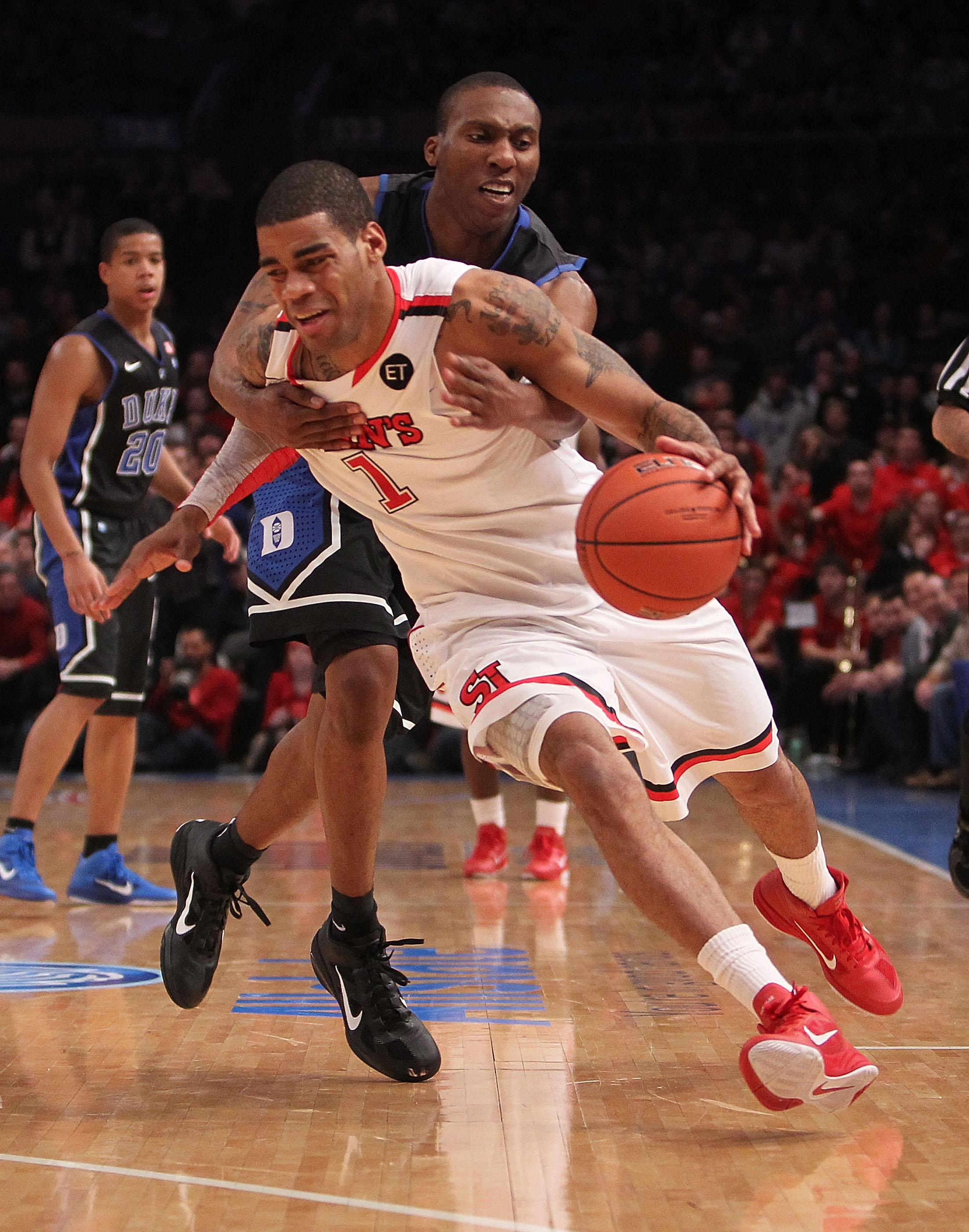 NEW YORK, NY - JANUARY 30:  D.J. Kennedy #1 of the St. John's Red Storm is fouled by Nolan Smith #2 of the Duke Blue Devils  at Madison Square Garden on January 30, 2011 in New York City.  (Photo by Nick Laham/Getty Images)