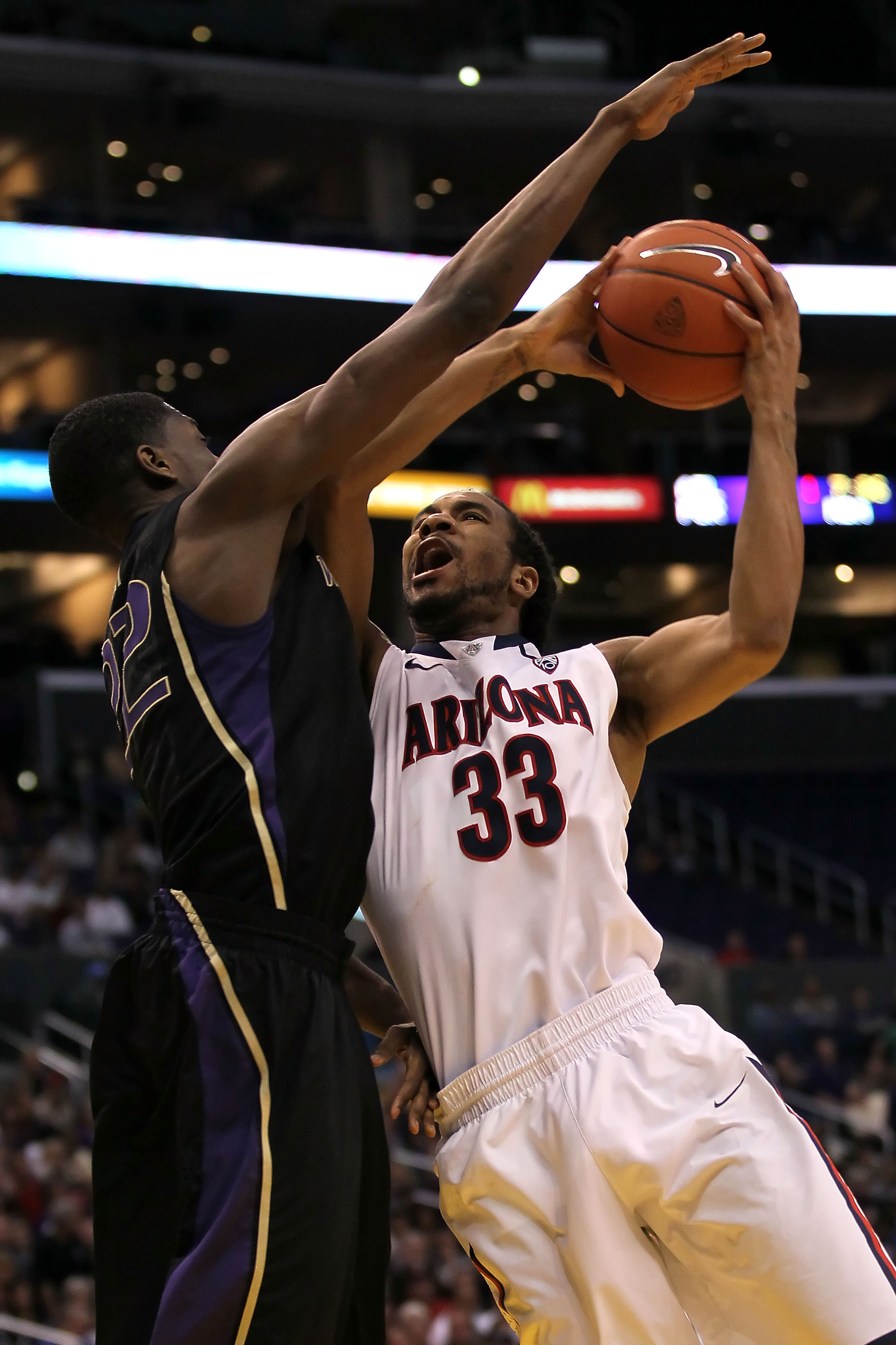 LOS ANGELES, CA - MARCH 12:  Jesse Perry #33 of the Arizona Wildcats shoots over Justin Holiday #22 of the Washington Huskies in the second half in the championship game of the 2011 Pacific Life Pac-10 Men's Basketball Tournament at Staples Center on Marc