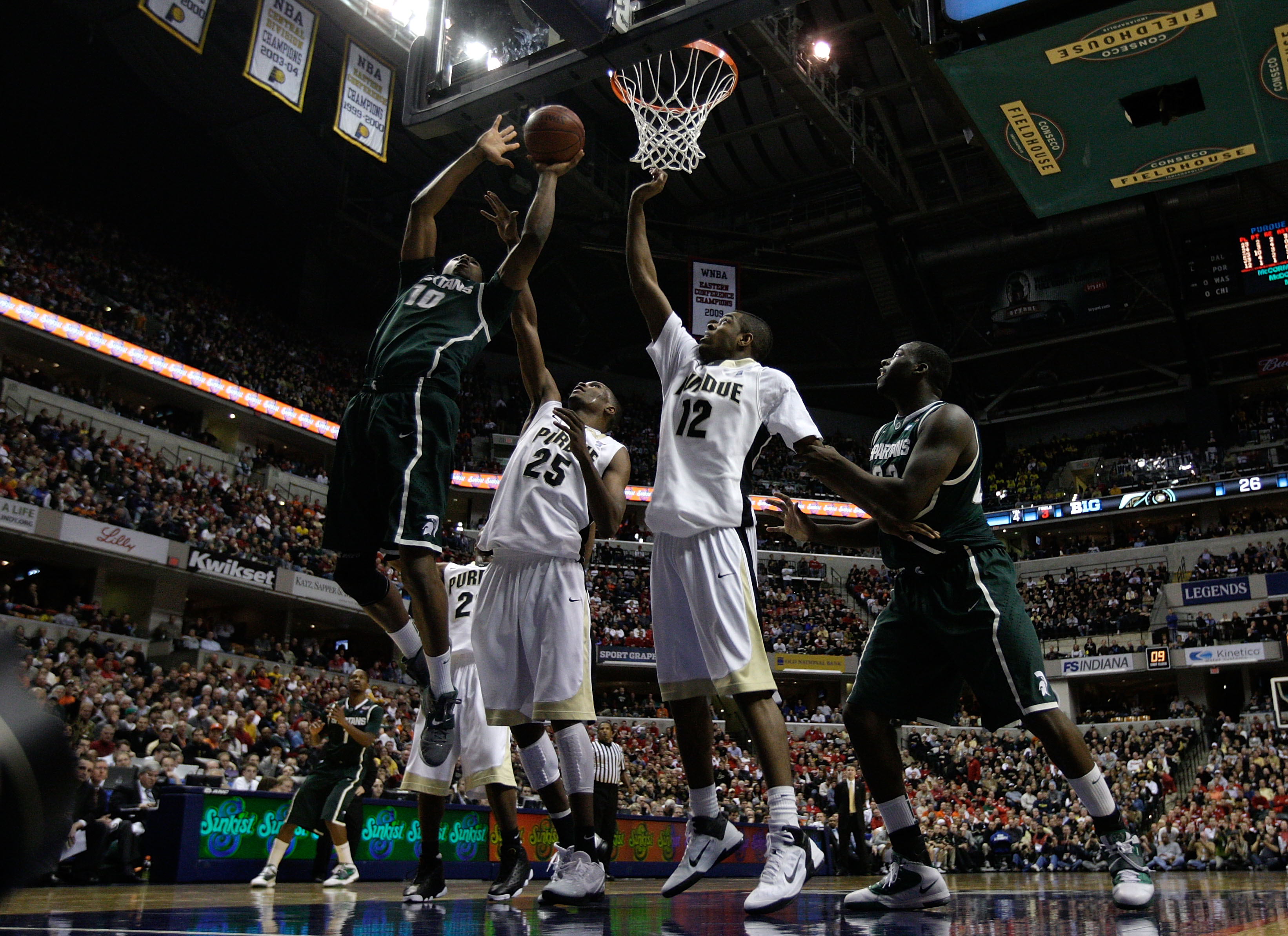 INDIANAPOLIS, IN - MARCH 11:  Delvon Roe #10 of the Michigan State Spartans attempts a shot against JaJuan Johnson #25 and Kelsey Barlow #12 of the Purdue Boilermakers during the quarterfinals of the 2011 Big Ten Men's Basketball Tournament at Conseco Fie