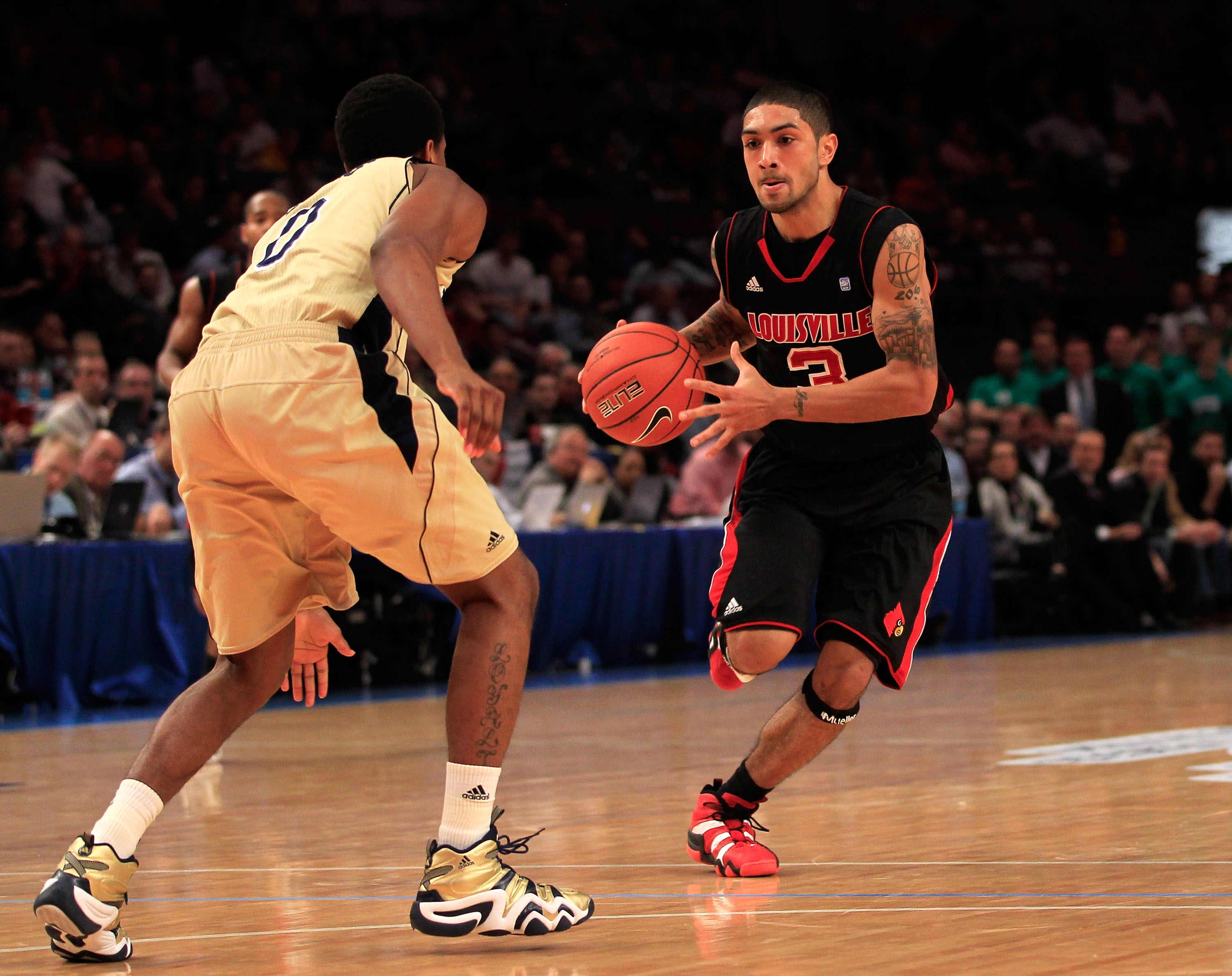 NEW YORK, NY - MARCH 11: Peyton Siva #3 of the Louisville Cardinals brings the ball up court against Eric Atkins #0 of the Notre Dame Fighting Irish  during the semifinals of the 2011 Big East Men's Basketball Tournament presented by American Eagle Outfit