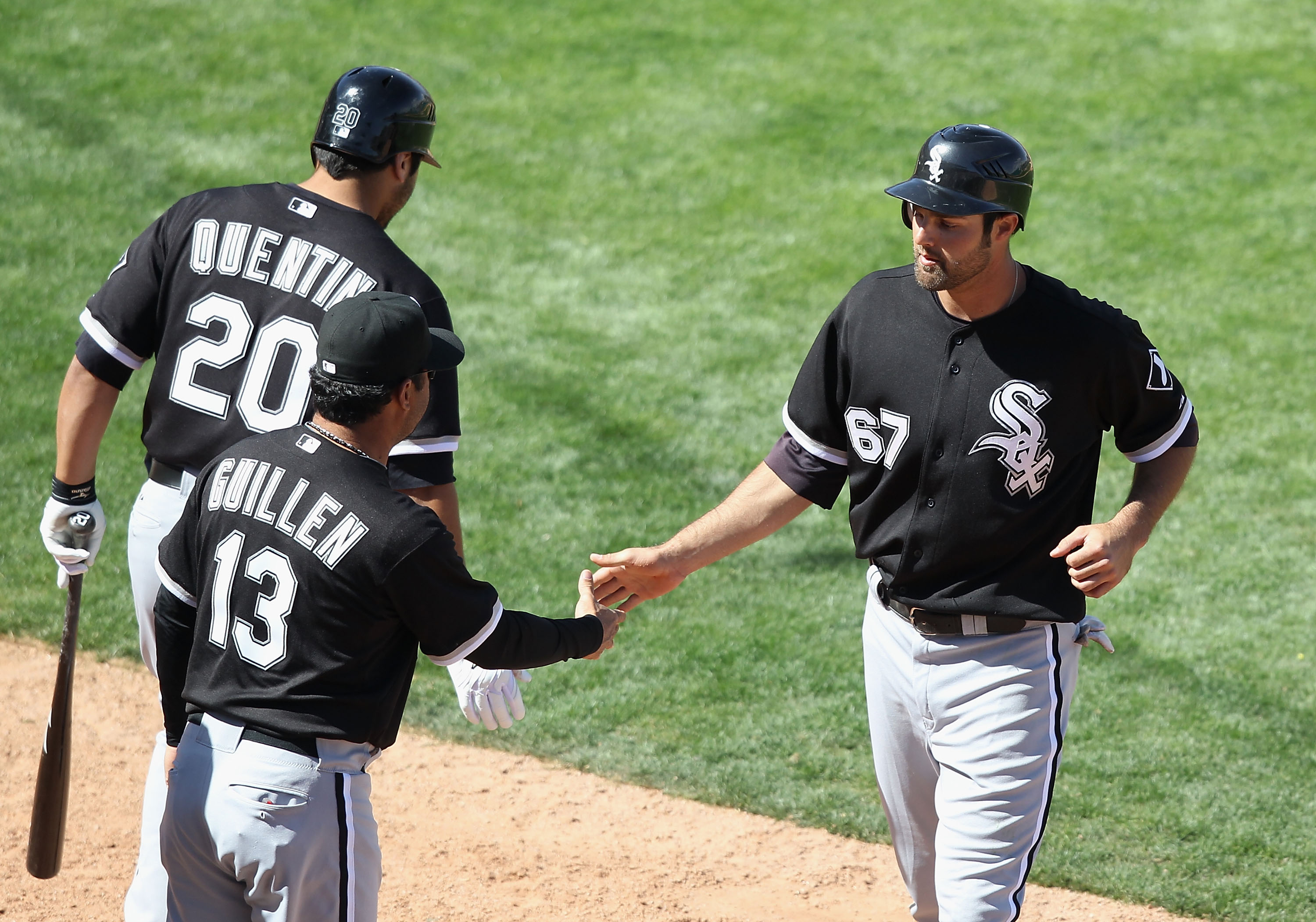 TUCSON, AZ - MARCH 07:   Jordan Danks #67 of the Chicago White Sox high fives manager Ozzie Guillen after Danks scored a run against the Arizona Diamondbacks during the fifth inning of the spring training game at Kino Veterans Memorial Stadium on March 7,