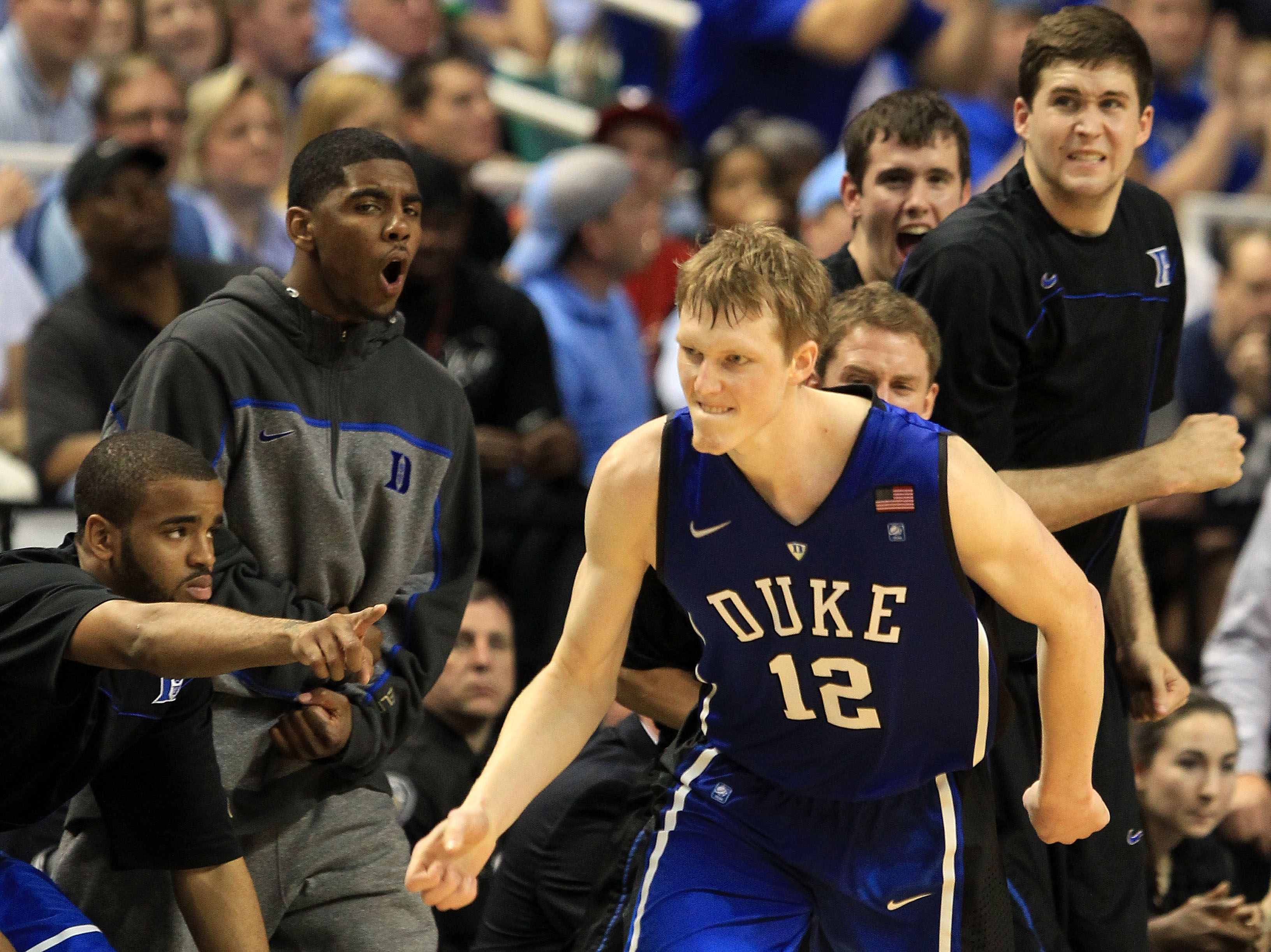 GREENSBORO, NC - MARCH 13:  Kyle Singler #12 of the Duke Blue Devils reacts as teammate Kyrie Irving #1 and the bench cheer him on during the second half of the game against the North Carolina Tar Heels in the championship game of the 2011 ACC men's baske