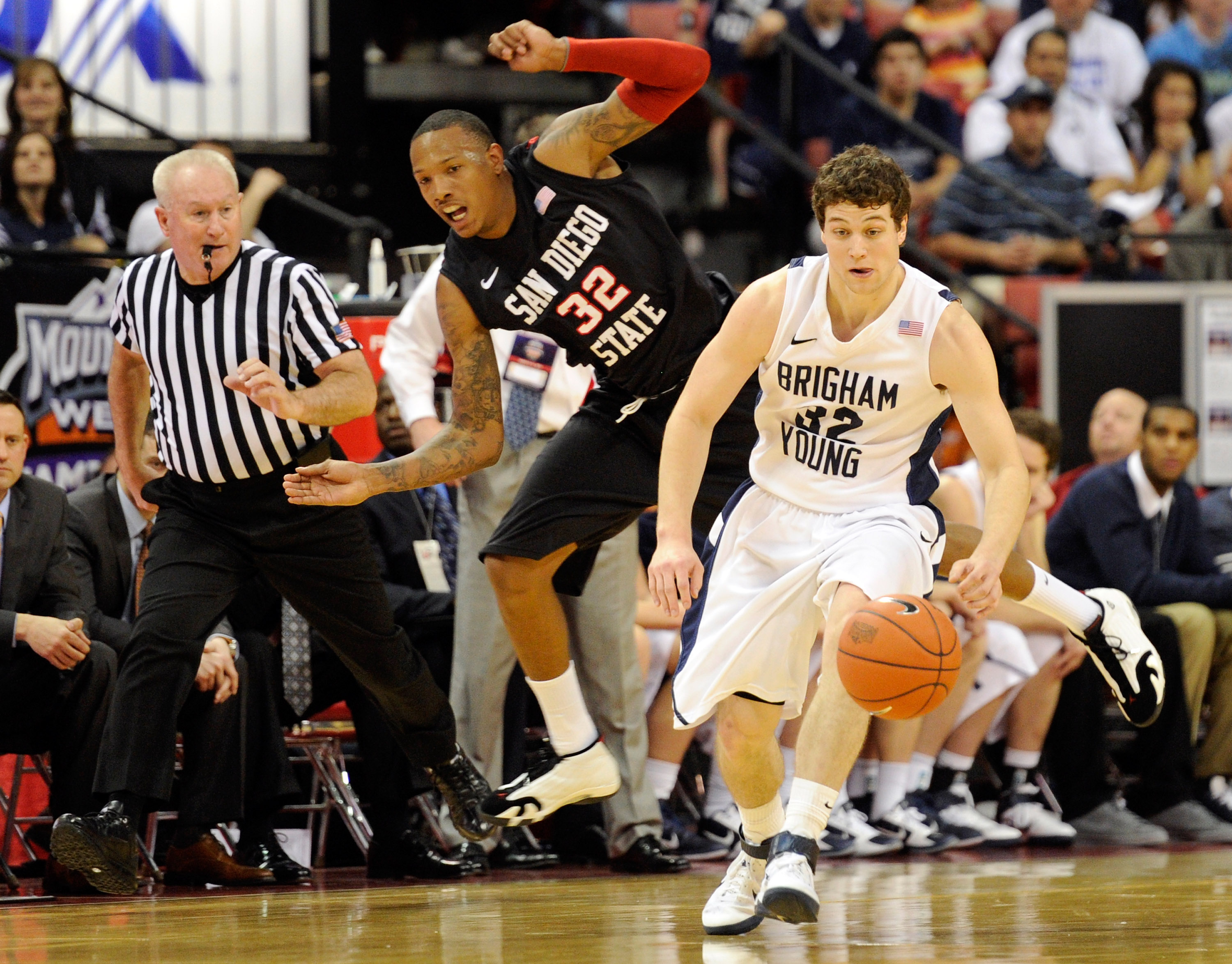LAS VEGAS, NV - MARCH 12:  Jimmer Fredette #32 of the Brigham Young University Cougars gets away from Billy White #32 of the San Diego State Aztecs during the championship game of the Conoco Mountain West Conference Basketball tournament at the Thomas & M