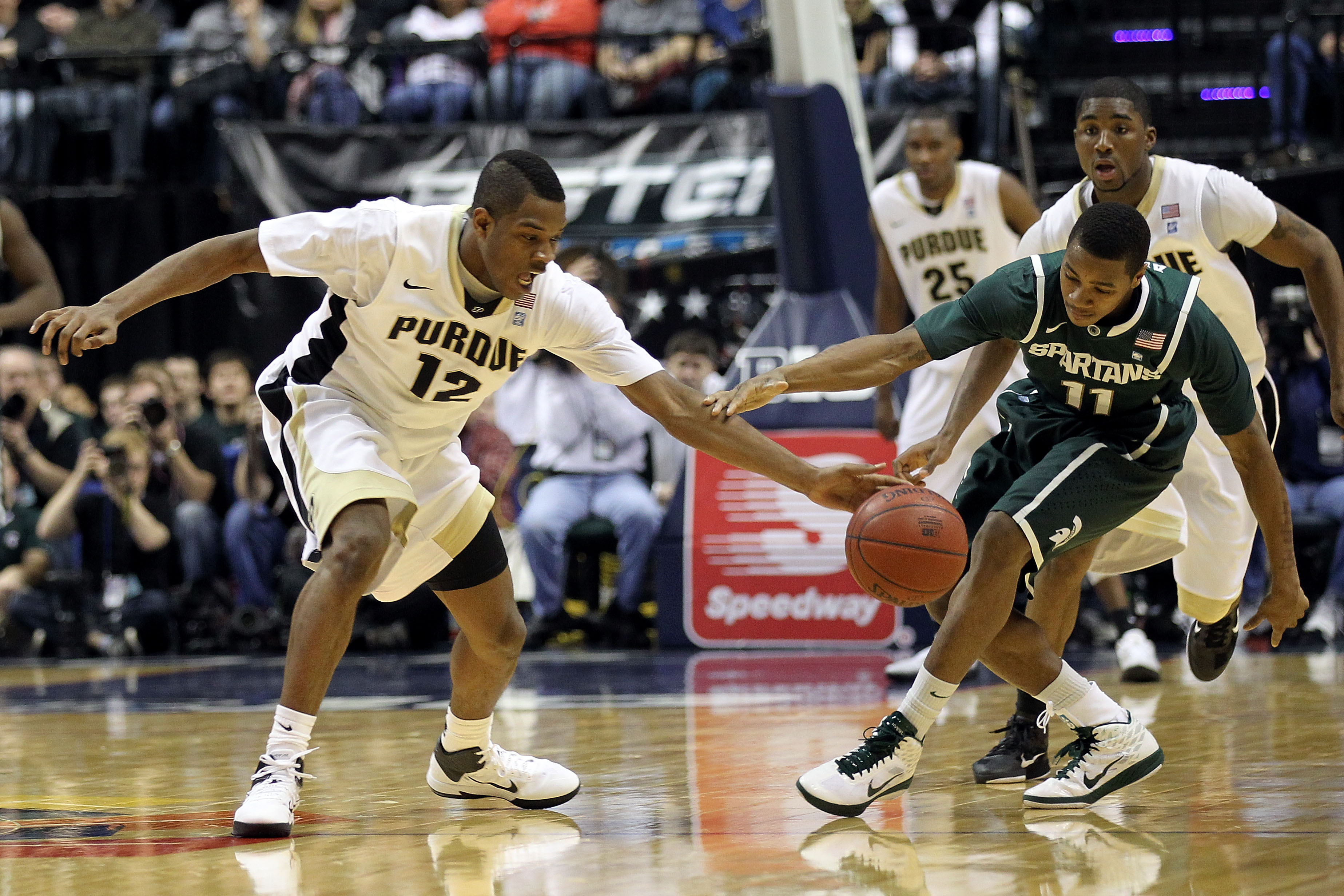 INDIANAPOLIS, IN - MARCH 11:  Kelsey Barlow #12 of the Purdue Boilermakers fights for a loose ball against Keith Appling #11 of the Michigan State Spartans during the quarterfinals of the 2011 Big Ten Men's Basketball Tournament at Conseco Fieldhouse on M
