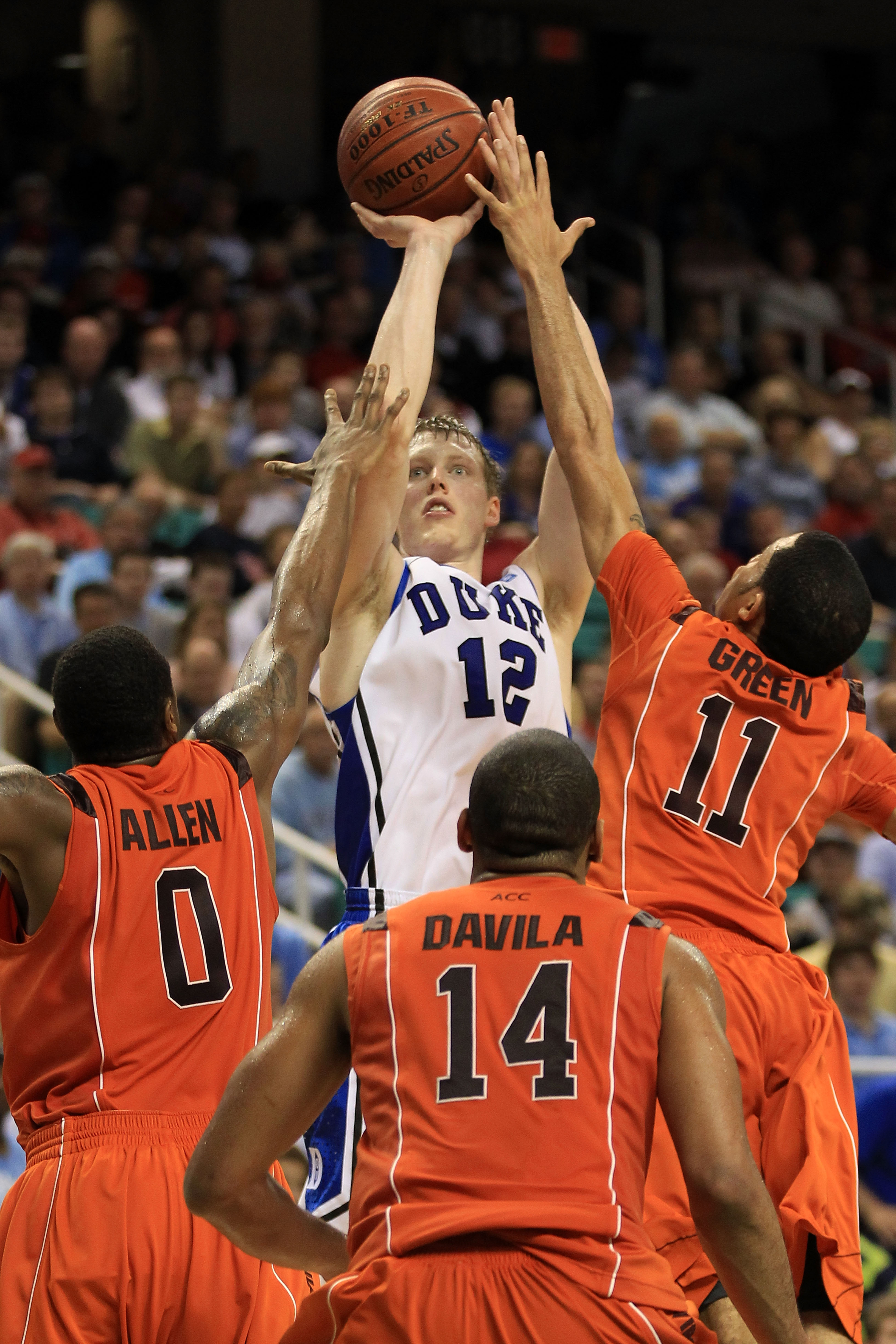 GREENSBORO, NC - MARCH 12:  Kyle Singler #12 of the Duke Blue Devils shoots against Jeff Allen #0, Victor Davila #14 and Erick Green #11 of the Virginia Tech Hokies during the first half in the semifinals of the 2011 ACC men's basketball tournament at the