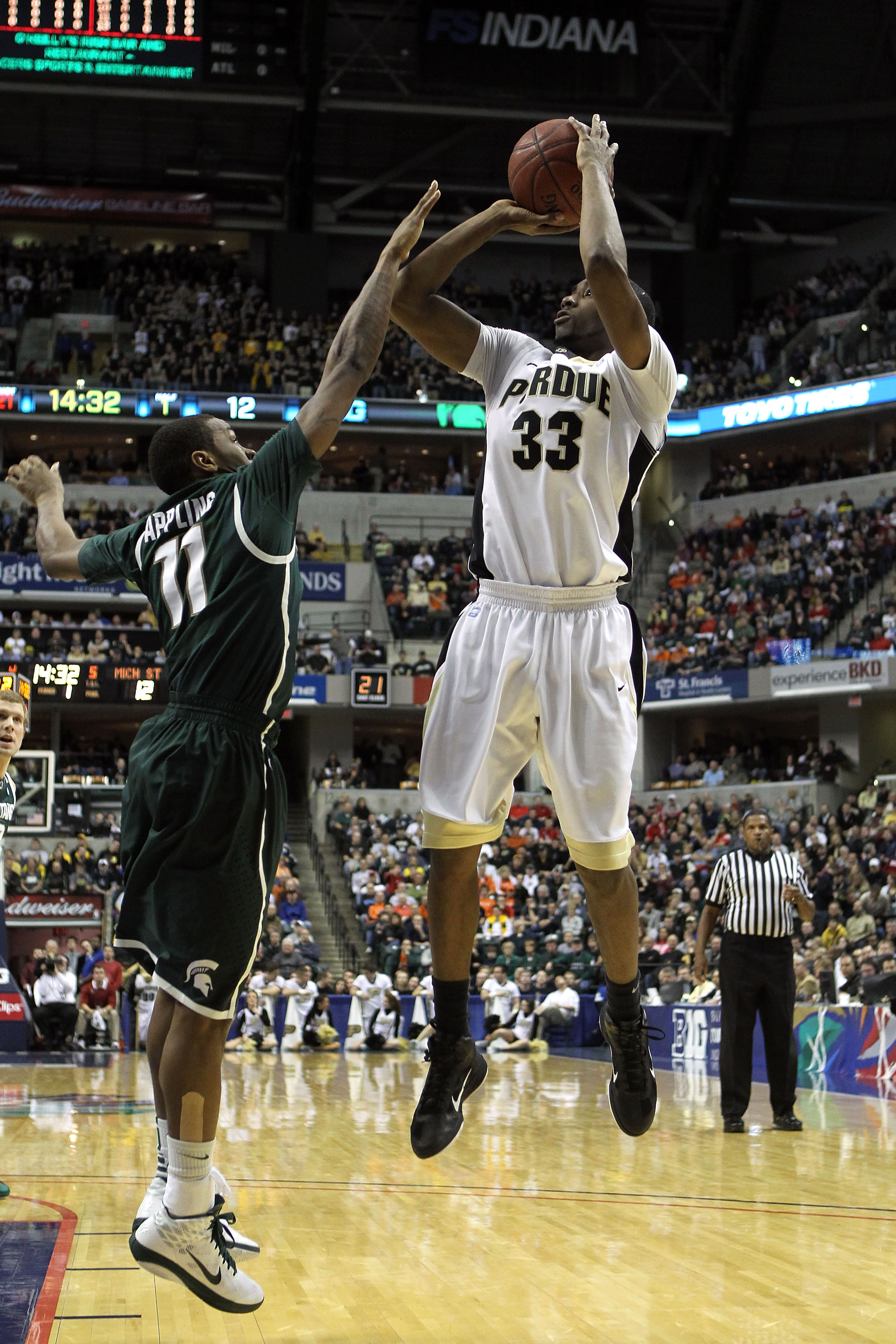 INDIANAPOLIS, IN - MARCH 11:  E'Twaun Moore #33 of the Purdue Boilermakers attempts a shot against Keith Appling #11 of the Michigan State Spartans during the quarterfinals of the 2011 Big Ten Men's Basketball Tournament at Conseco Fieldhouse on March 11,