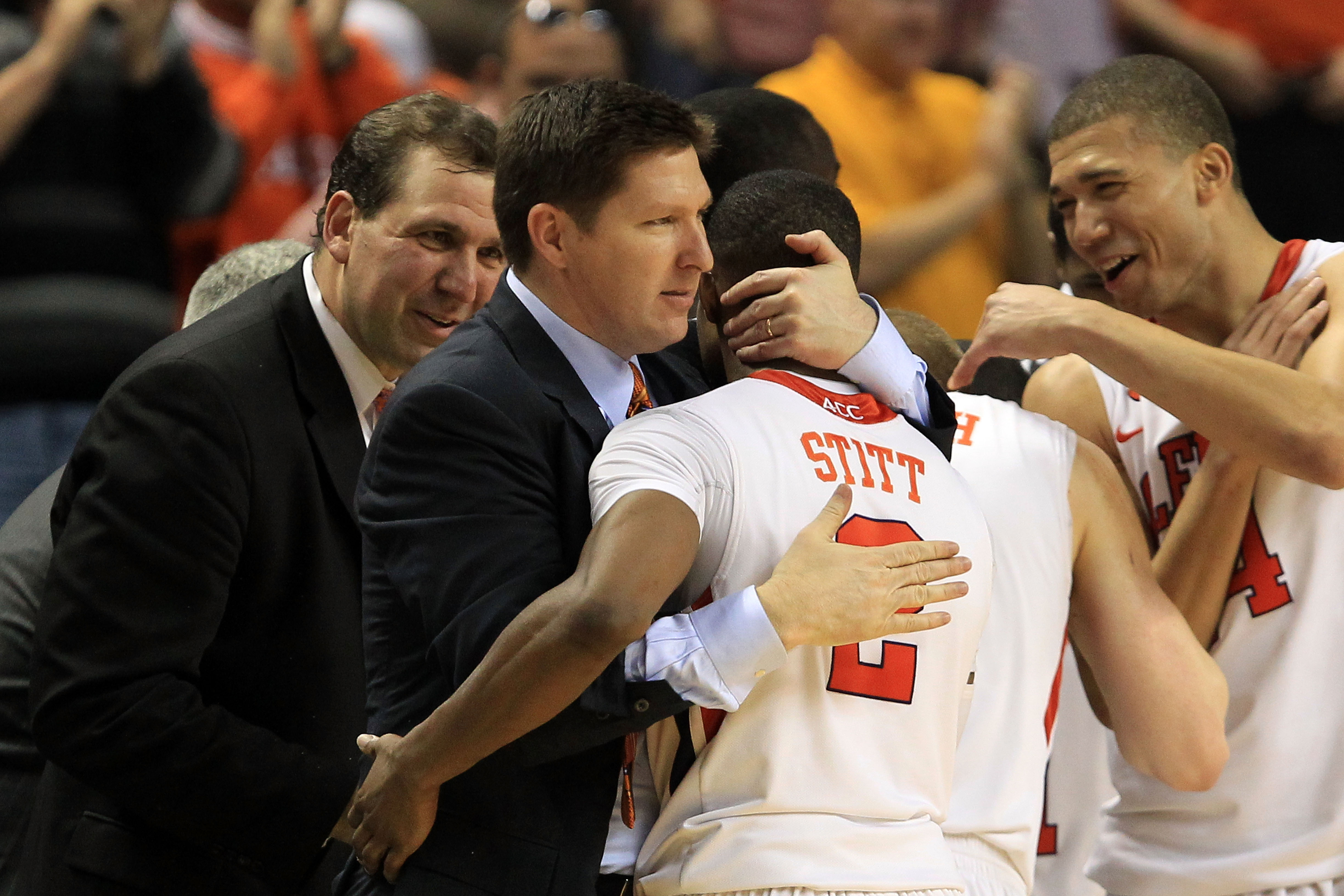 GREENSBORO, NC - MARCH 11:  Head coach Brad Brownell of the Clemson Tigers hugs player Demontez Stitt #2 after their 70-47 victory over the Boston College Eagles during the second half in the quarterfinals of the 2011 ACC men's basketball tournament at th