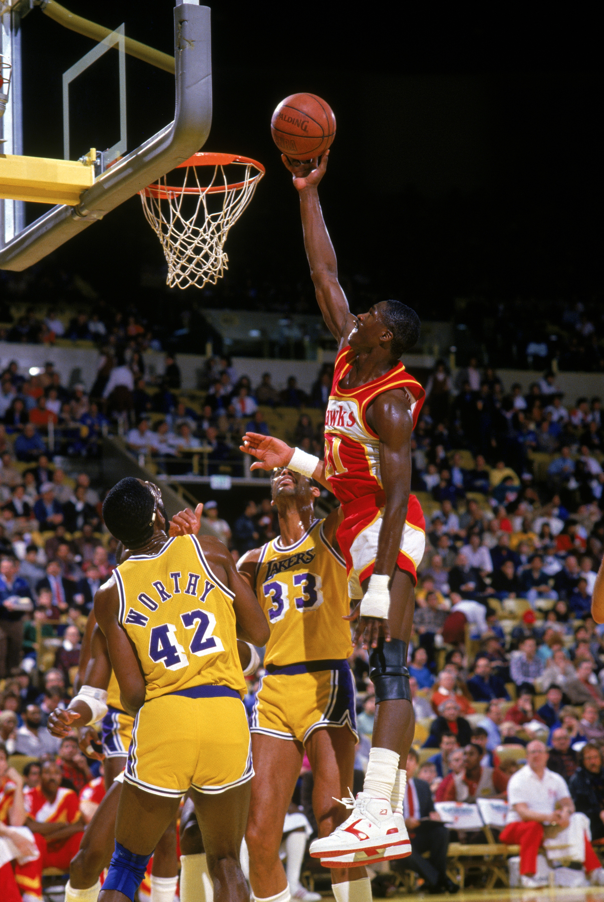 INGLEWOOD, CA - 1986:  Dominique Wilkins #21 of the Atlanta Hawks goes up for a layup against James Worthy #42 and Kareem Abdul-Jabbar #33 of the Los Angeles Lakers during a 1986 NBA season game at the Great Western Forum in Inglewood, California.   (Phot