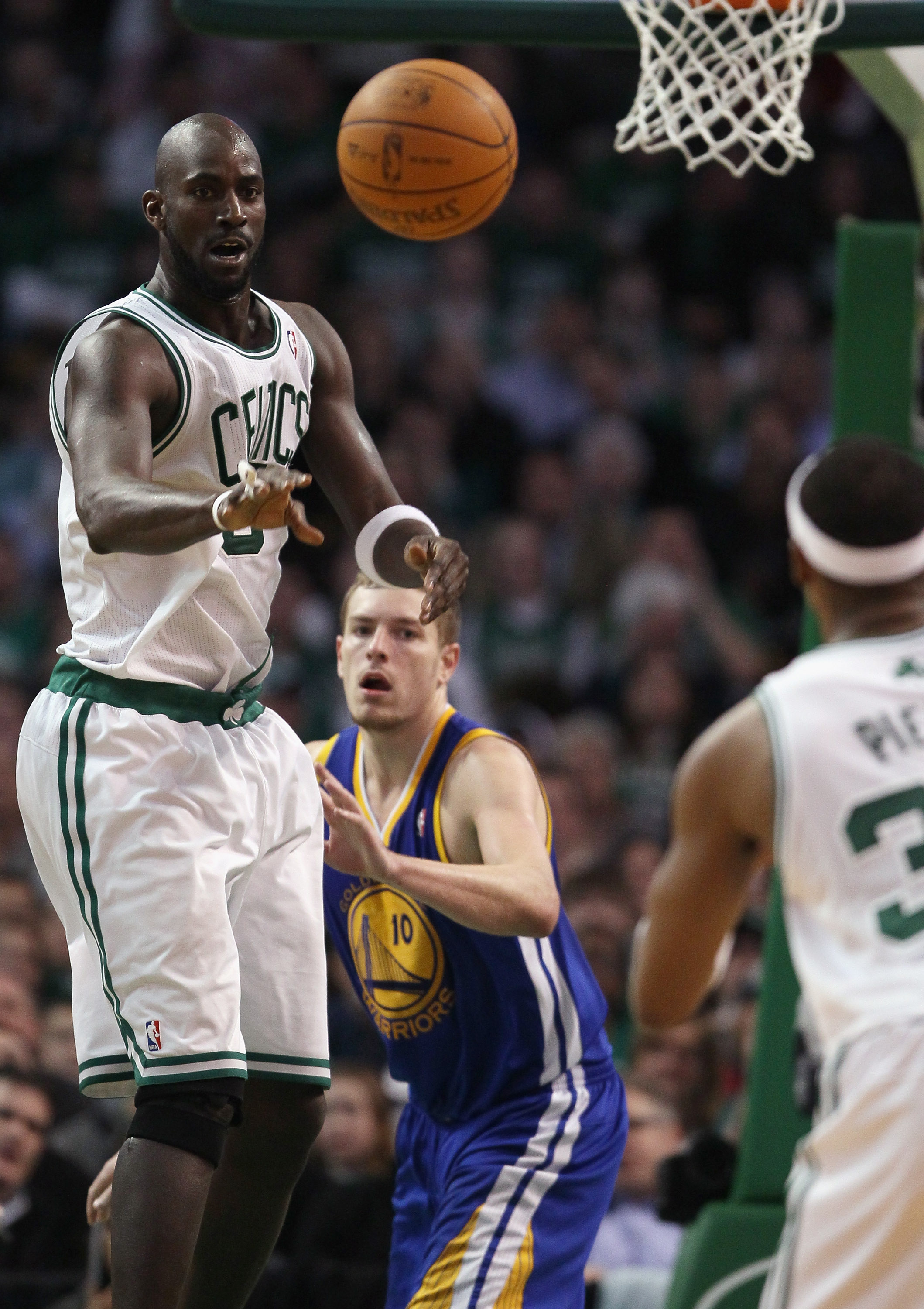 BOSTON, MA - MARCH 04: Kevin Garnett #5 of the Boston Celtics passes the ball to Paul Pierce #34 as David Lee #10 of the Golden State Warriors defends on March 4, 2011 at the TD Garden in Boston, Massachusetts.  The Celtics defeated the Warriors 107-103.