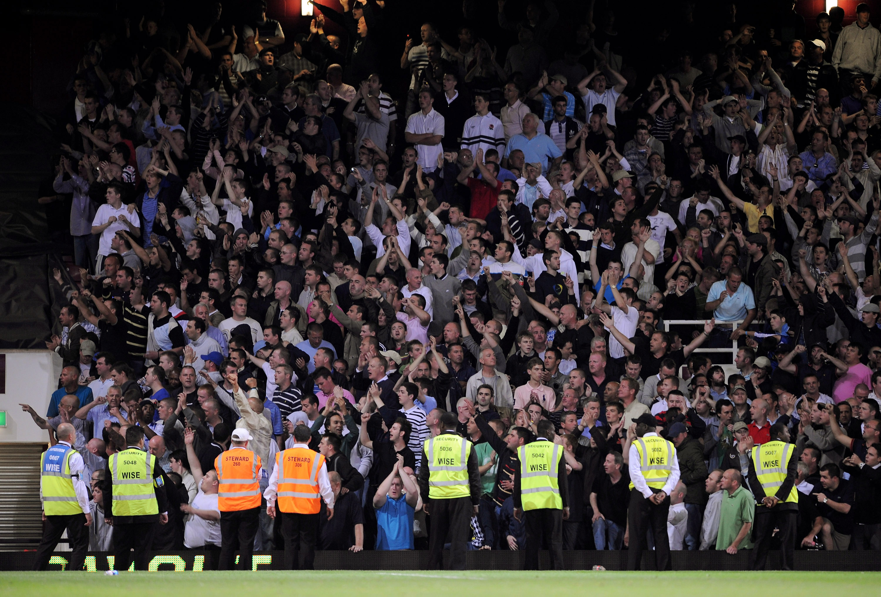 LONDON, ENGLAND - AUGUST 25:  Stewards stand infront of the Millwall fans during the Carling Cup second round match between West Ham United and Millwall at Upton Park on August 25, 2009 in London, England. . Violence broke out between West Ham and Millwal