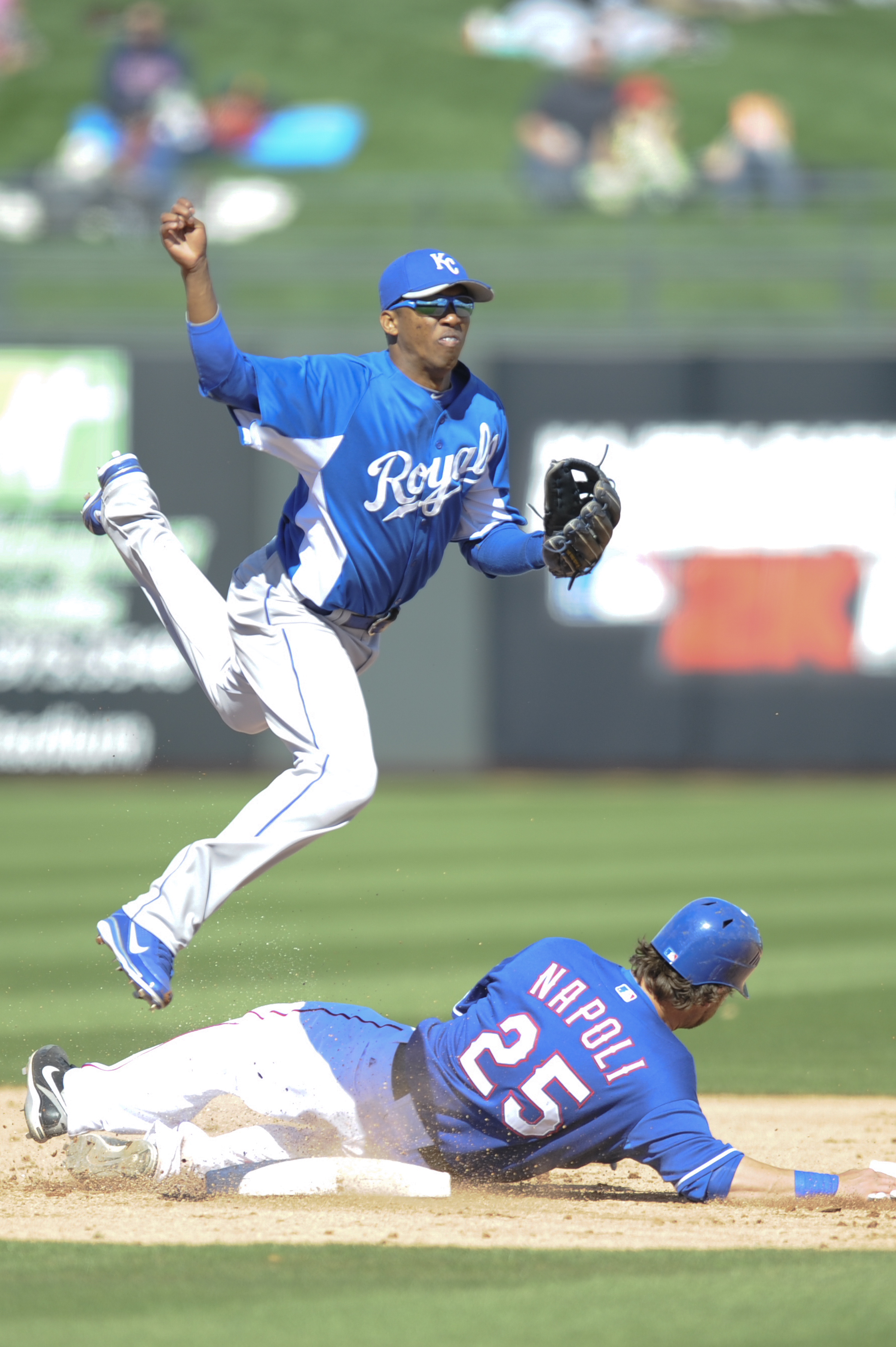 SURPISE, AZ - FEBRUARY 27: Alcides Escobar #2 of the Kansas City Royals attempts to complete a double play during a spring training game as Mike Napoli #25 of the Texas Rangers slides into him at Surprise Stadium on February 27, 2011 in Surprise, Arizona.