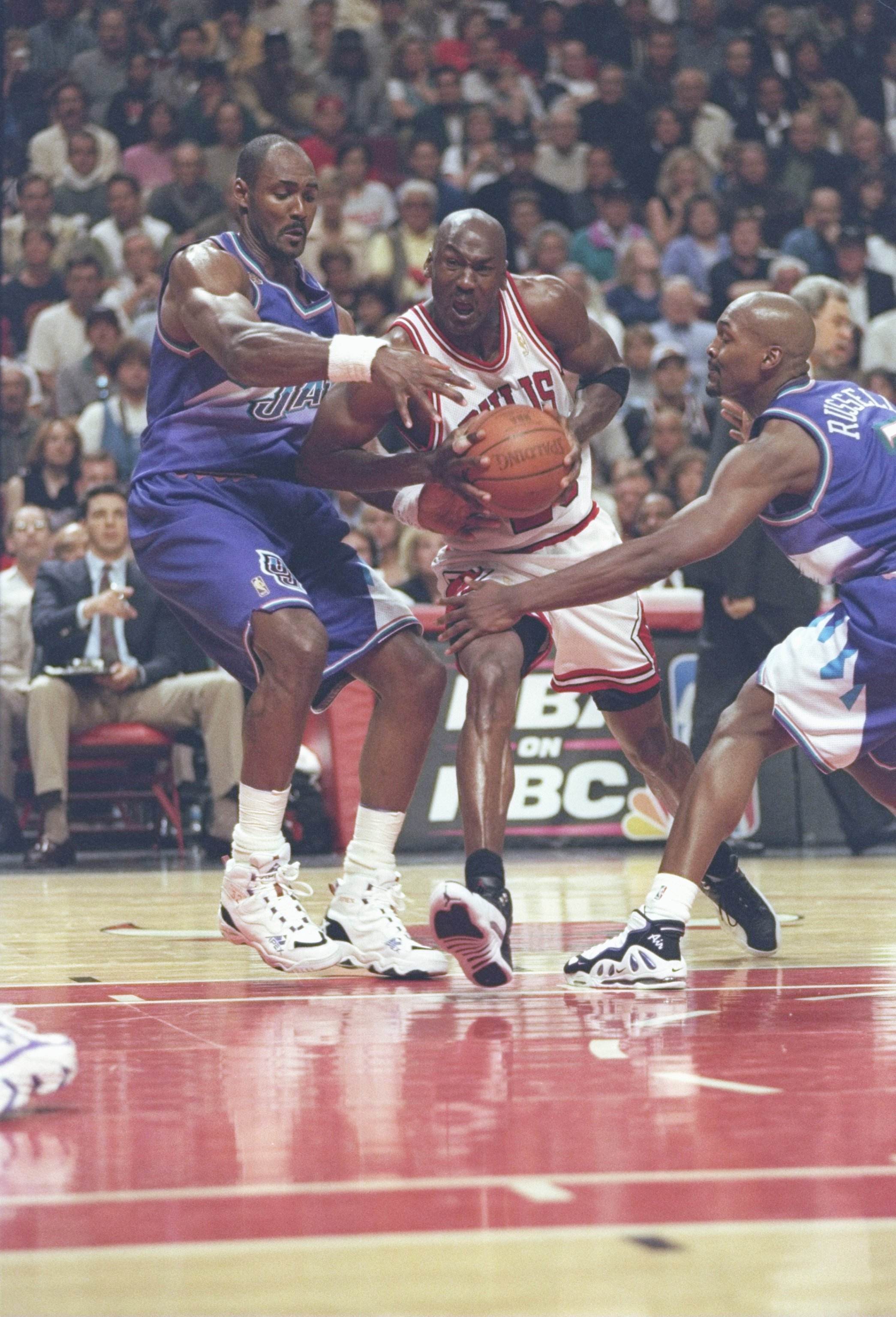 13 Jun 1997: Guard Michael Jordan of the Chicago Bulls drives between forward Karl Malone and forward Bryon Russell of the Utah Jazz during game 6 of the 1997 NBA Finals at the United Center in Chicago, Illinois. The Bulls defeated the Jazz 90-86 to win t