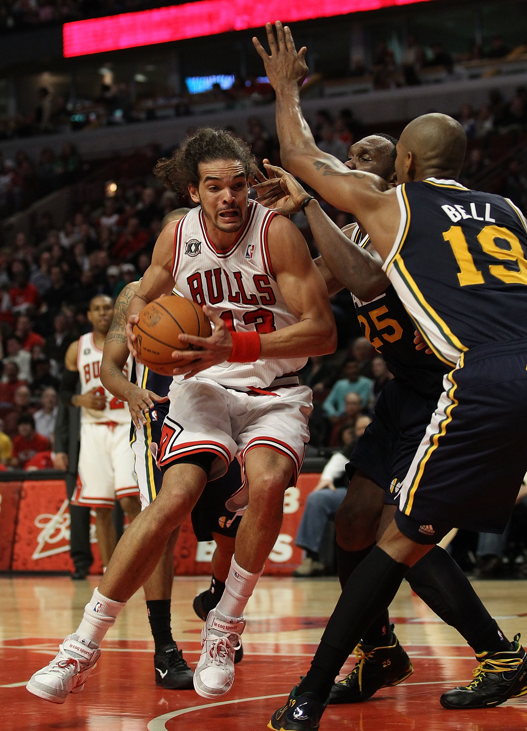 CHICAGO, IL - MARCH 12: Joakim Noah #13 of the Chicago Bulls drives against Al Jefferson #25 and Raja Bell #19 of the Utah Jazz at the United Center on March 12, 2011 in Chicago, Illinois. The Bulls defeated the Jazz 118-100. NOTE TO USER: User expressly