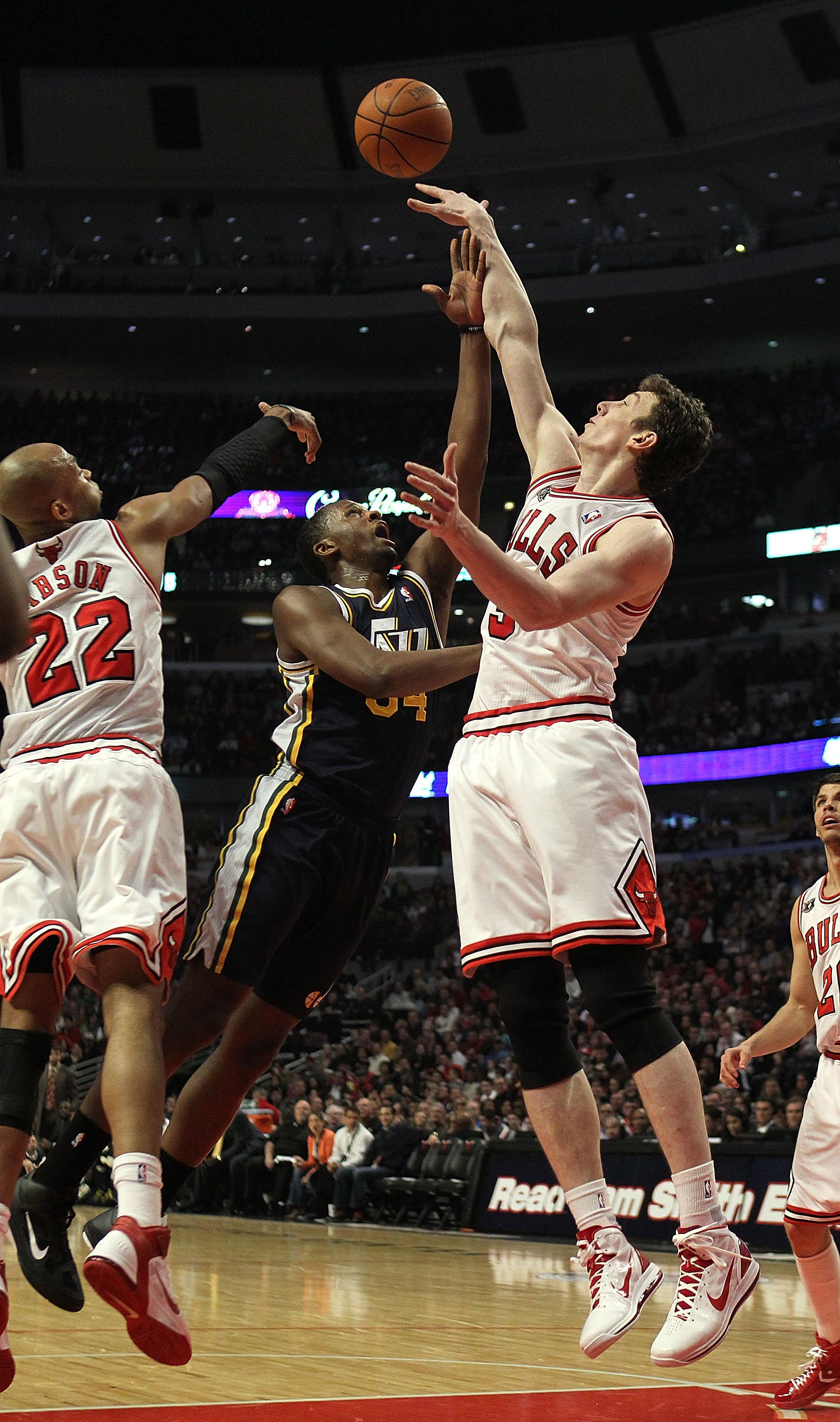 CHICAGO, IL - MARCH 12: Omer Asik #3 of the Chicago Bulls blocks a shot by C.J. Miles #34 of the Utah Jazz as Taj Gibson #22 also defends at the United Center on March 12, 2011 in Chicago, Illinois. NOTE TO USER: User expressly acknowledges and agrees tha