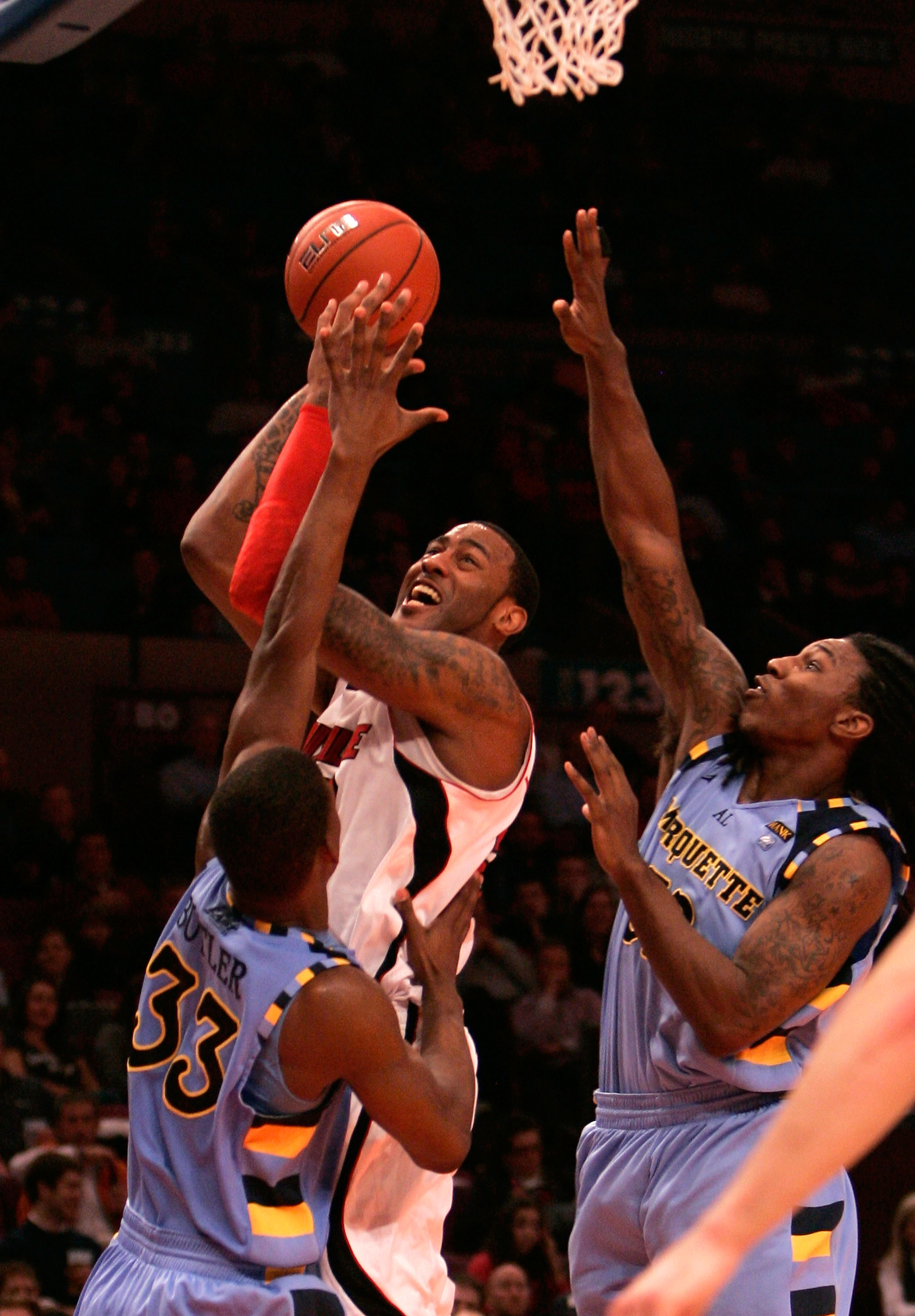NEW YORK, NY - MARCH 10:  Terrence Jennings #23 of the Louisville Cardinals drives to the basket against Jimmy Butler #33 and Jae Crowder #32 of the Marquette Golden Eagles during the quarterfinals of the 2011 Big East Men's Basketball Tournament presente