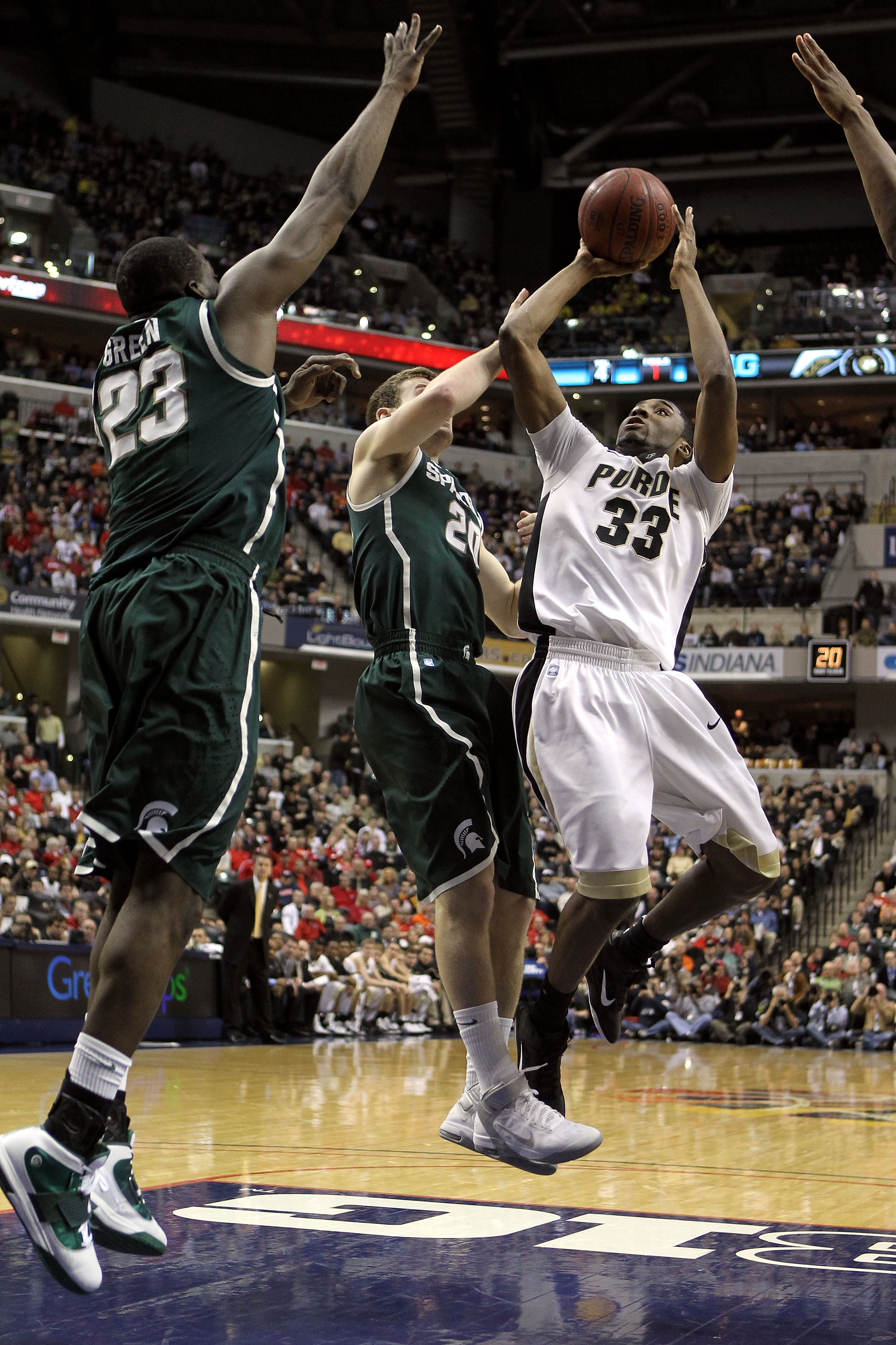 INDIANAPOLIS, IN - MARCH 11:  E'Twaun Moore #33 of the Purdue Boilermakers attempts a shot in the first half against Mike Kebler #20 and Draymond Green #23 of the Michigan State Spartans during the quarterfinals of the 2011 Big Ten Men's Basketball Tourna