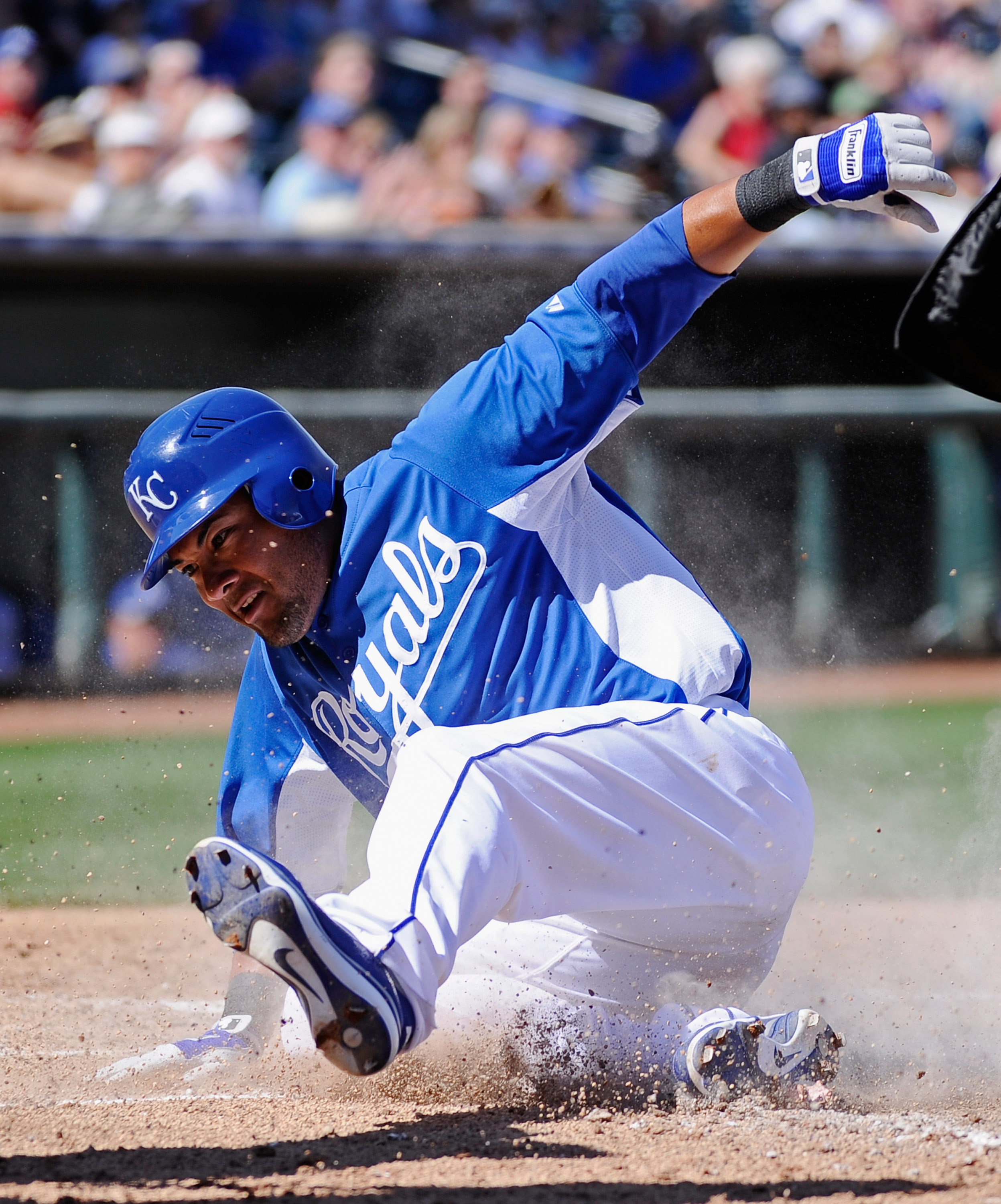 SURPRISE, AZ - MARCH 12:  Melky Cabrera #53 of the Kansas City Royals slides at home plate to score a run during the fourth inning of the spring training baseball game against the Los Angeles Dodgers at Surprise Stadium on March 12, 2011 in Surprise, Ariz