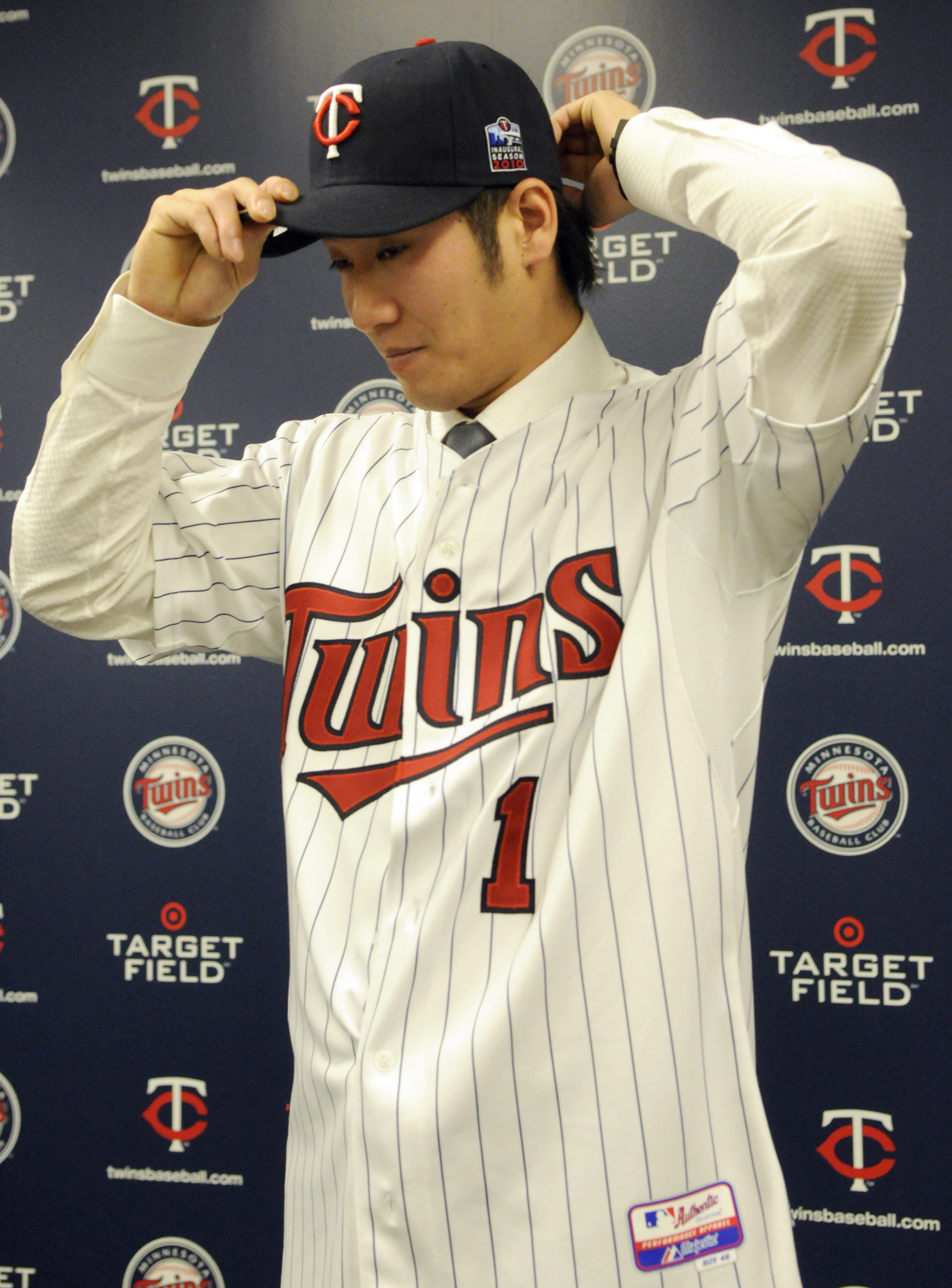MINNEAPOLIS, MN - DECEMBER 18: Tsuyoshi Nishioka #1 of the Minnesota Twins puts on his Twins hats for members of the media during a press conference on December 18, 2010 at Target Field in Minneapolis, Minnesota. (Photo by Hannah Foslien /Getty Images)