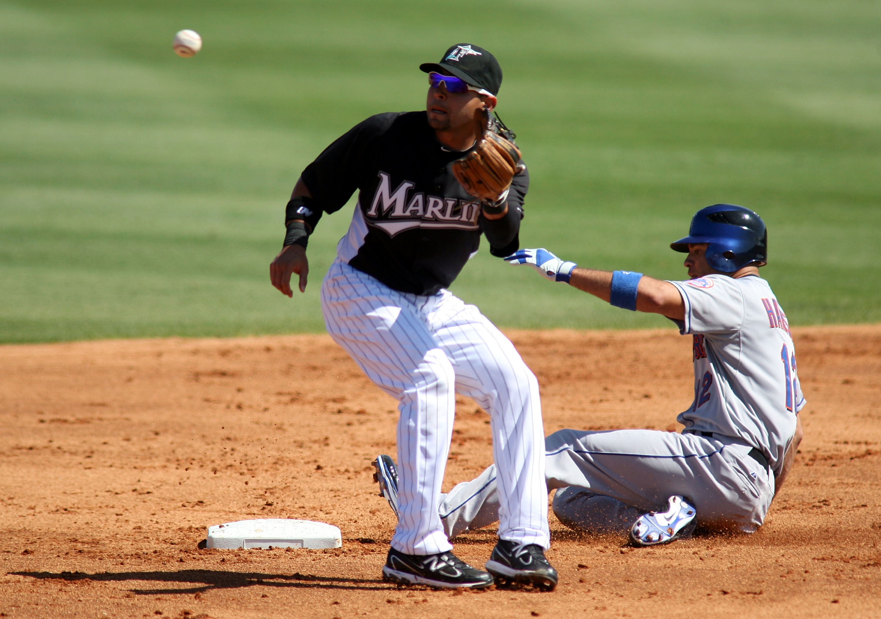 JUPITER, FL - MARCH 04:   Scott Hairston #12 of the New York Mets slides safely against second baseman Omar Infante #13 of the Florida Marlins at Roger Dean Stadium on March 4, 2011 in Jupiter, Florida.  (Photo by Marc Serota/Getty Images)