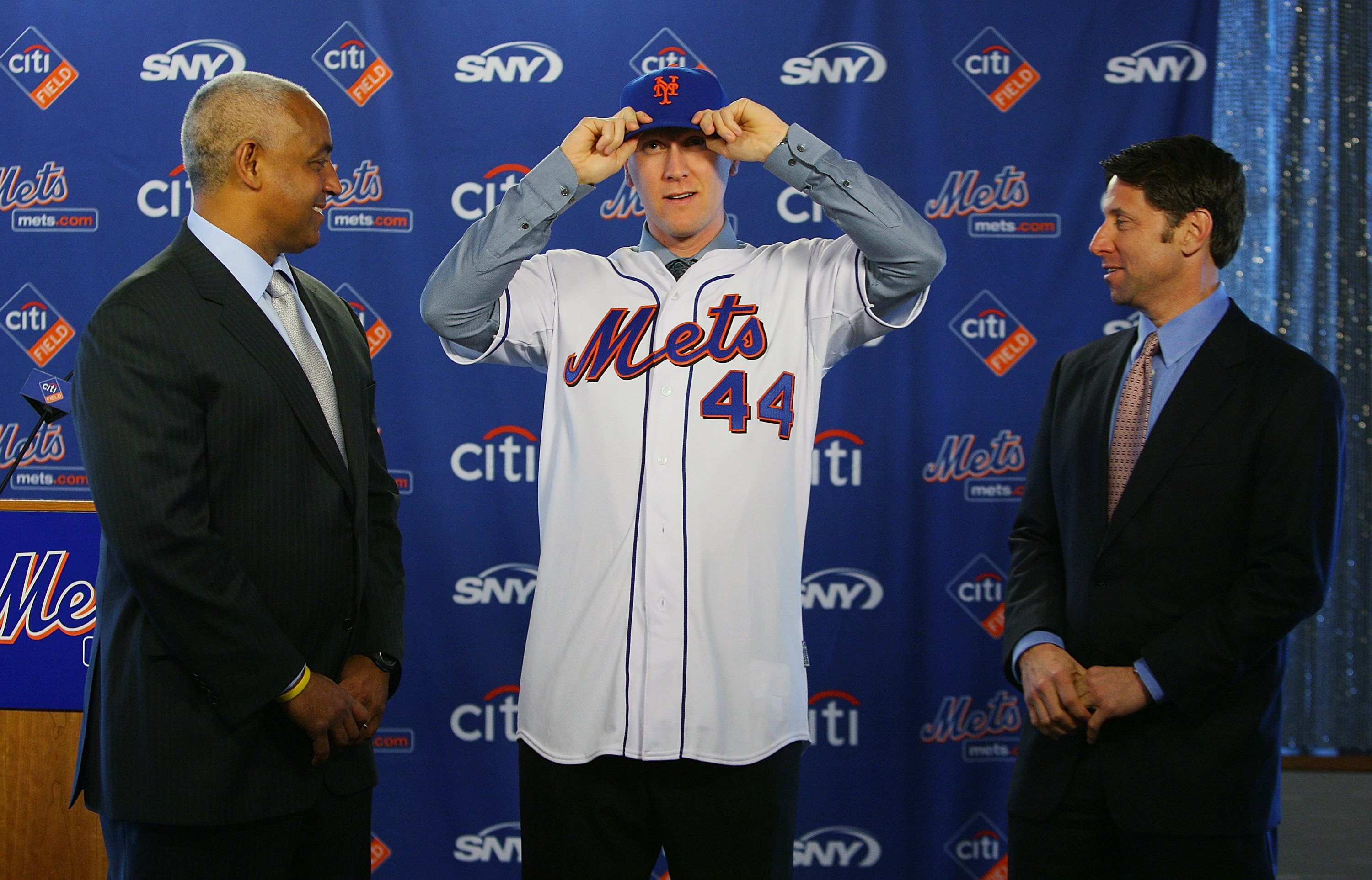 NEW YORK - JANUARY 05:  (L-R) General Manager Omar Minaya watches Jason Bay and put on a New York Mets hat as Mets COO Jeff Wilpon looks on during a press conference to announce Bay's signing to the New York Mets on January 5, 2010 at Citi Field in the Fl