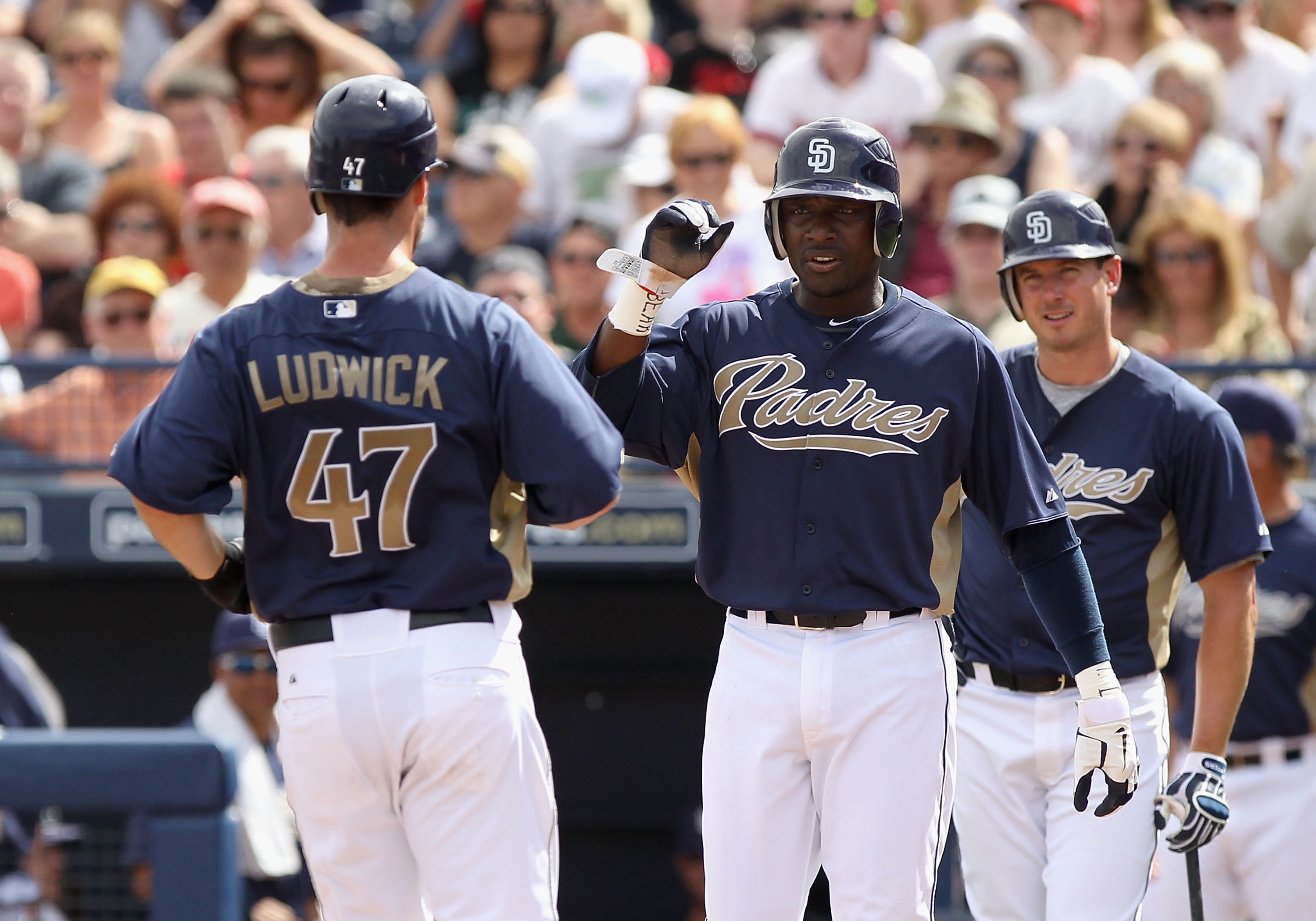 PEORIA, AZ - MARCH 15:  Ryan Ludwick #47 of the San Diego Padres is congratulated by teammates Orlando Hudson #1 and Brad Hawpe #11 after hitting a 2 run home run against the Los Angeles Angels of Anaheim during the third inning of the spring training gam