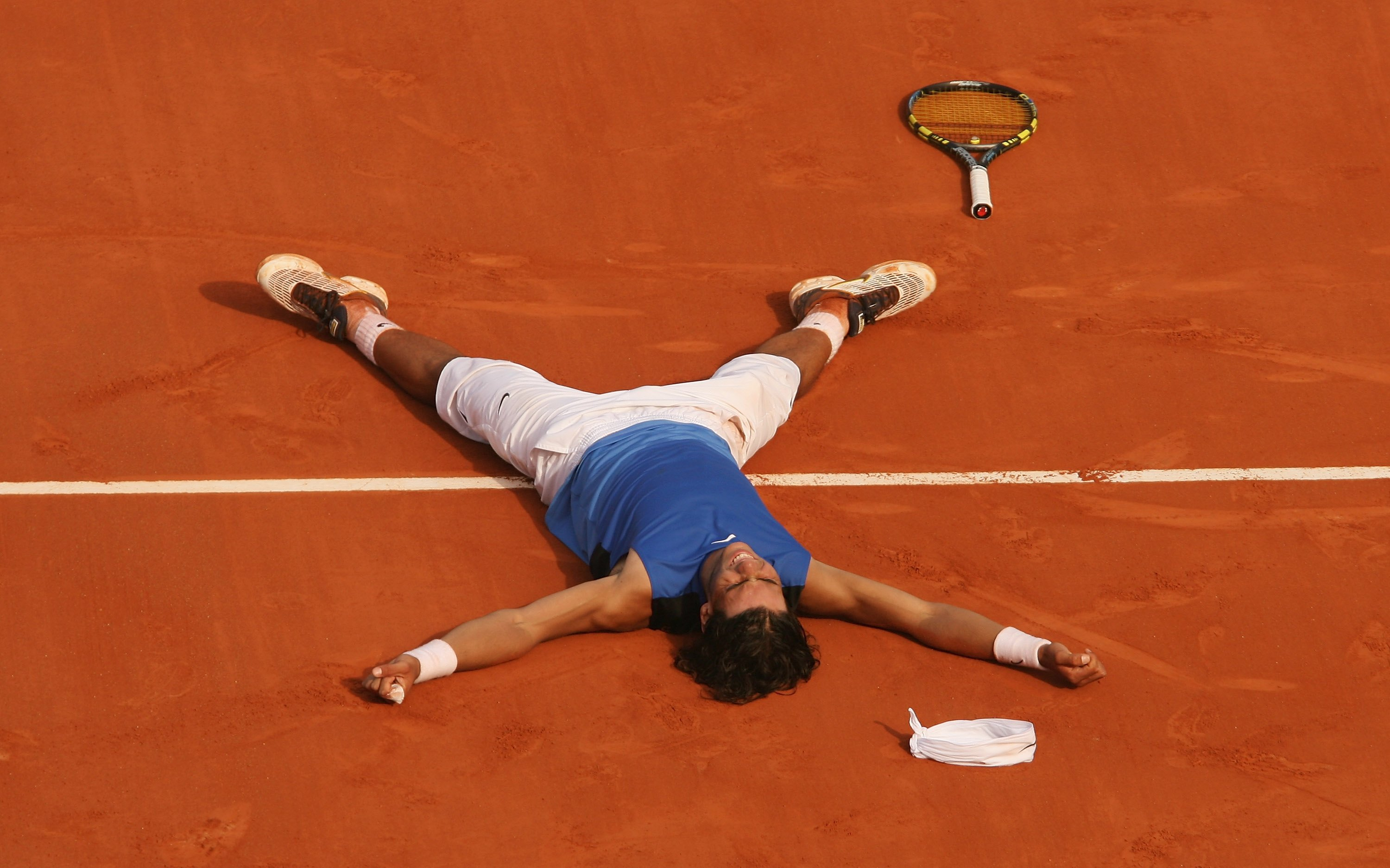 PARIS - JUNE 11:  Rafael Nadal of Spain lies on the clay after defeating Roger Federer of Switzerland during the Men's Singles Final on day fifteen of the French Open at Roland Garros on June 11, 2006 in Paris, France.  (Photo by Clive Brunskill/Getty Ima