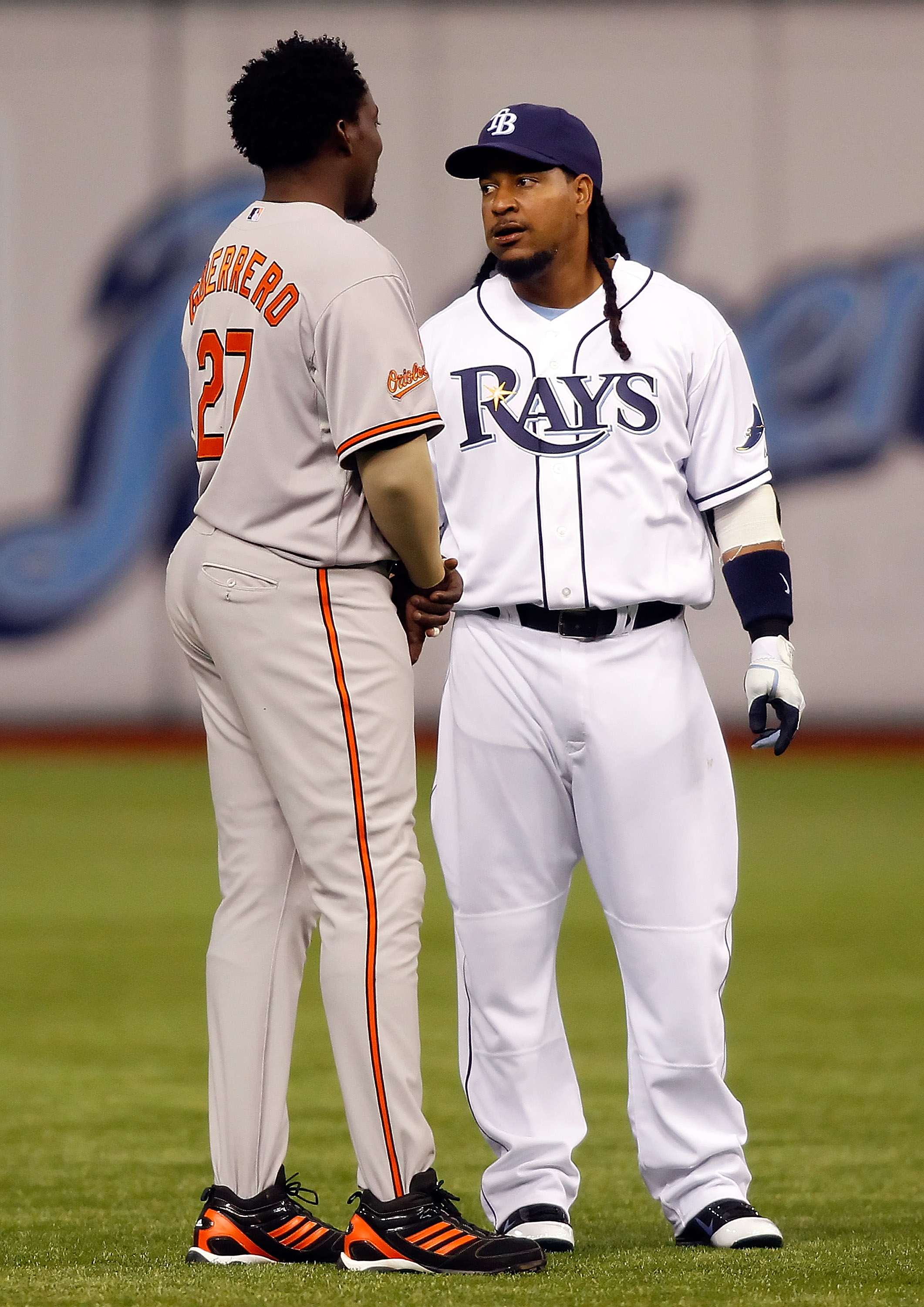 ST. PETERSBURG, FL - APRIL 02:  Designated hitter Manny Ramirez #24 of the Tampa Bay Rays talks with designated hitter Vladimir Guerrero #27 of the Baltimore Orioles just before the start of the game at Tropicana Field on April 2, 2011 in St. Petersburg,