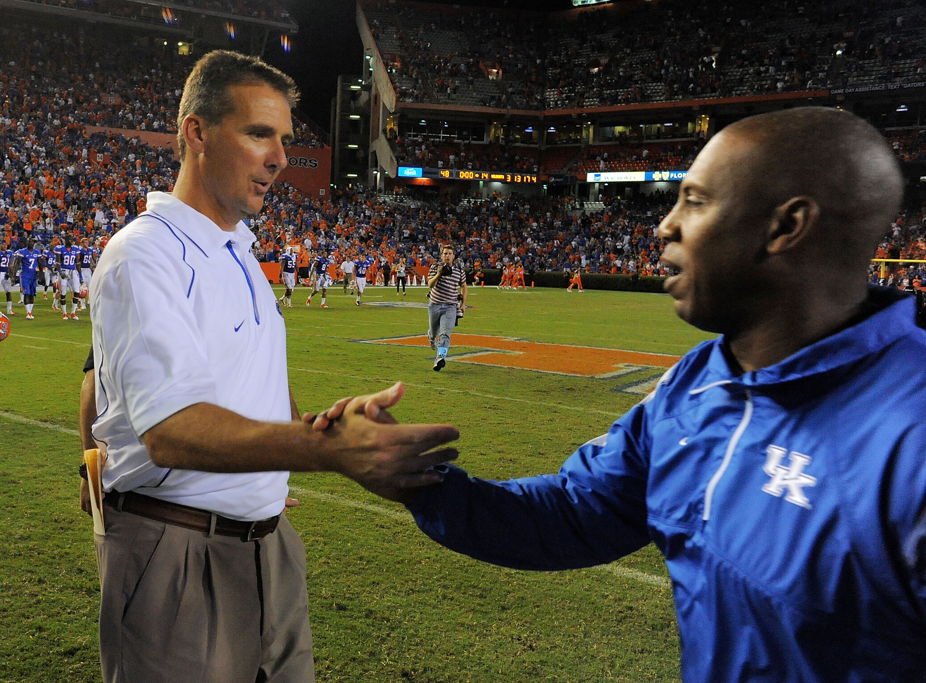 GAINESVILLE, FL - SEPTEMBER 25:  Head coach Urban Meyer of the Florida Gators is congratulated by head coach Joker Phillips of the Kentucky Wildcats at Ben Hill Griffin Stadium on September 25, 2010 in Gainesville, Florida. Florida defeated Kentucky 48-14