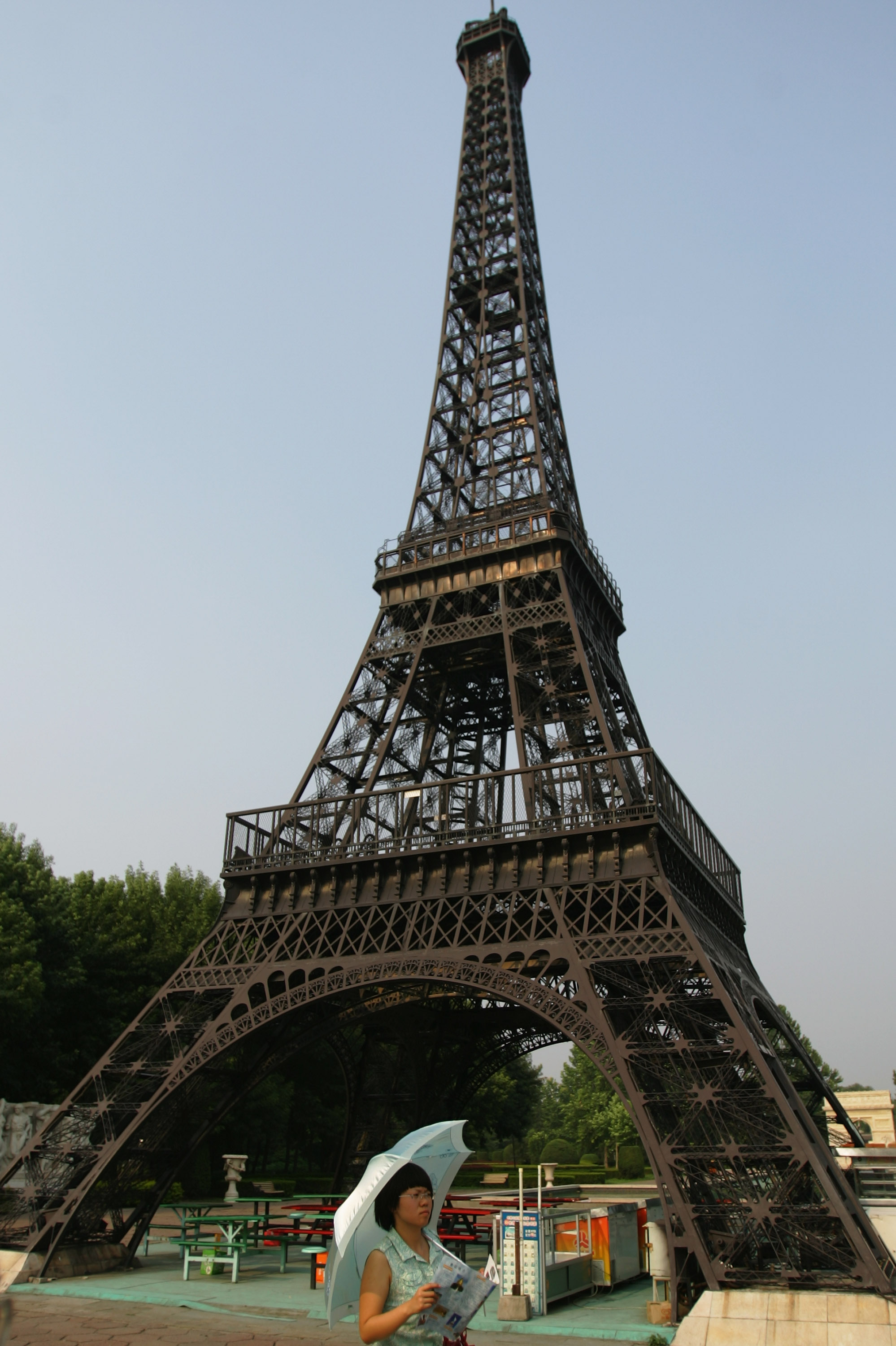 BEIJING - JULY 23:  A Chinese tourist walks under a replica of the Eiffel Tower at the World Park on July 23, 2008 in Beijing, China. The World Park is one of three parks designated for protesters parading during Beijing Olympic Games, according to China