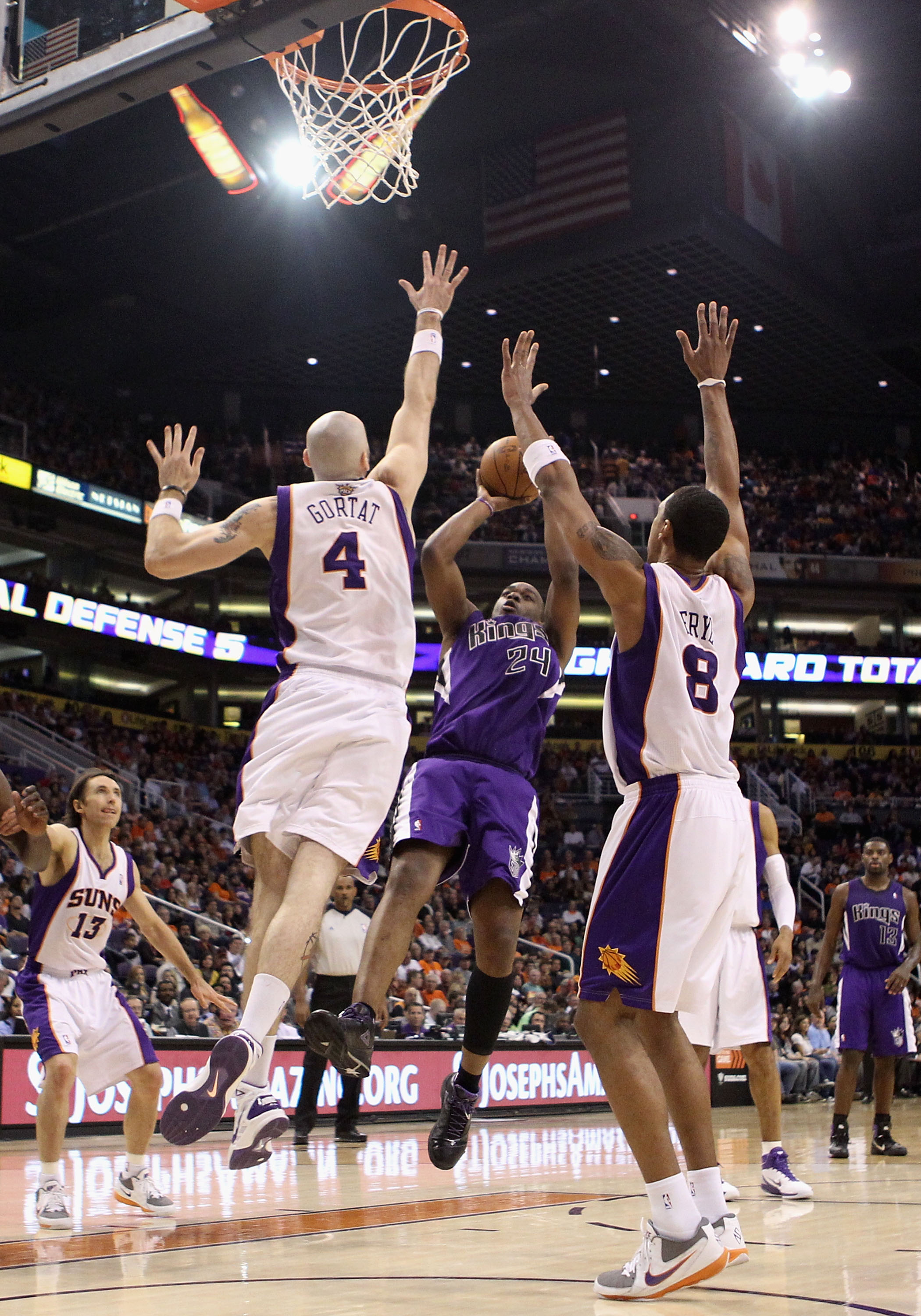 PHOENIX, AZ - FEBRUARY 13:  Carl Landry #24 of the Sacramento Kings puts up a shot against Marcin Gortat #4 and Channing Frye #8 of the Phoenix Suns during the NBA game at US Airways Center on February 13, 2011 in Phoenix, Arizona. The Kings defeated the