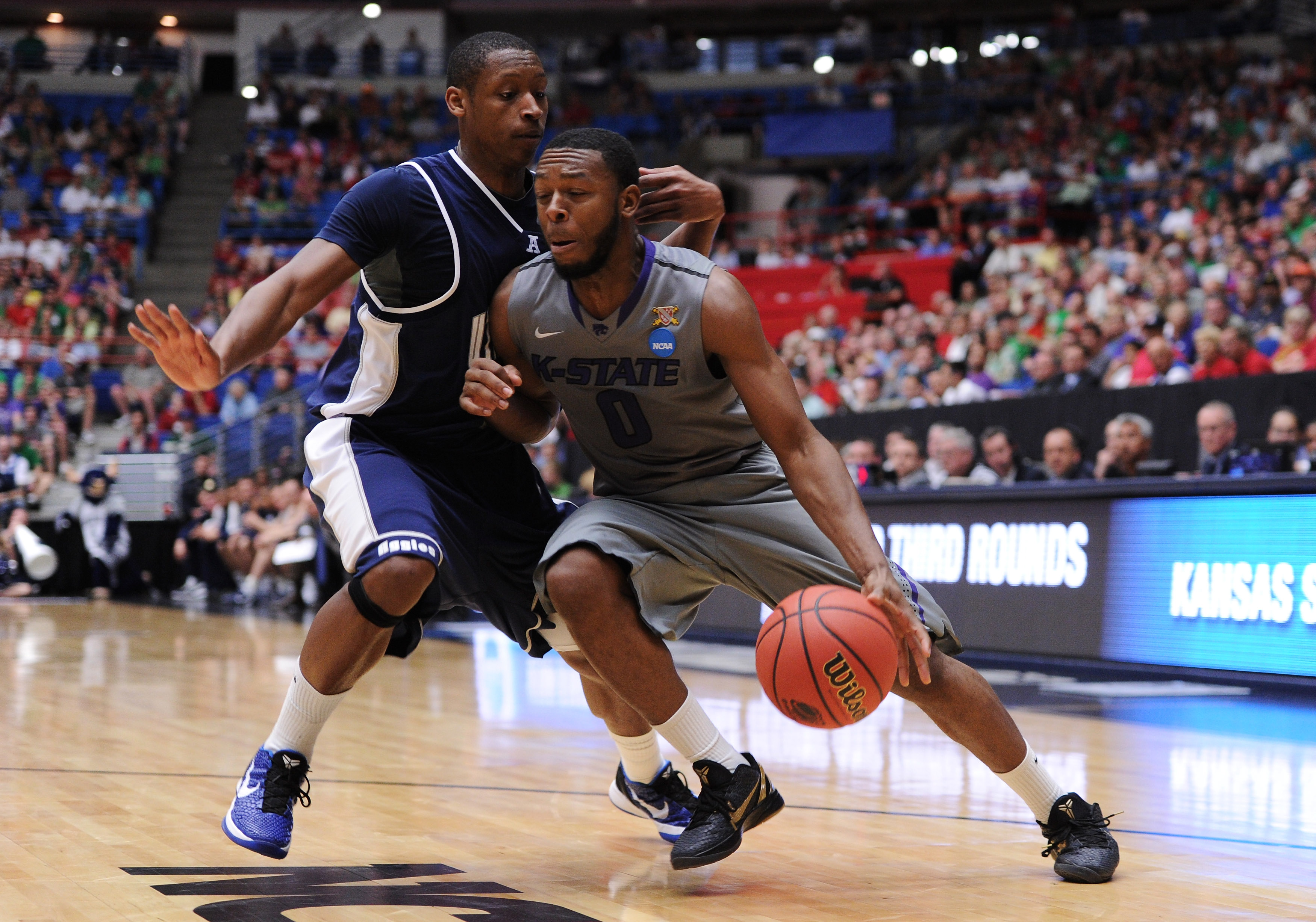 TUCSON, AZ - MARCH 17:  Jacob Pullen #0 of the Kansas State Wildcats drives against Pooh Williams #5 of the Utah State Aggies during the second round of the 2011 NCAA men's basketball tournament at McKale Center on March 17, 2011 in Tucson, Arizona.  (Pho
