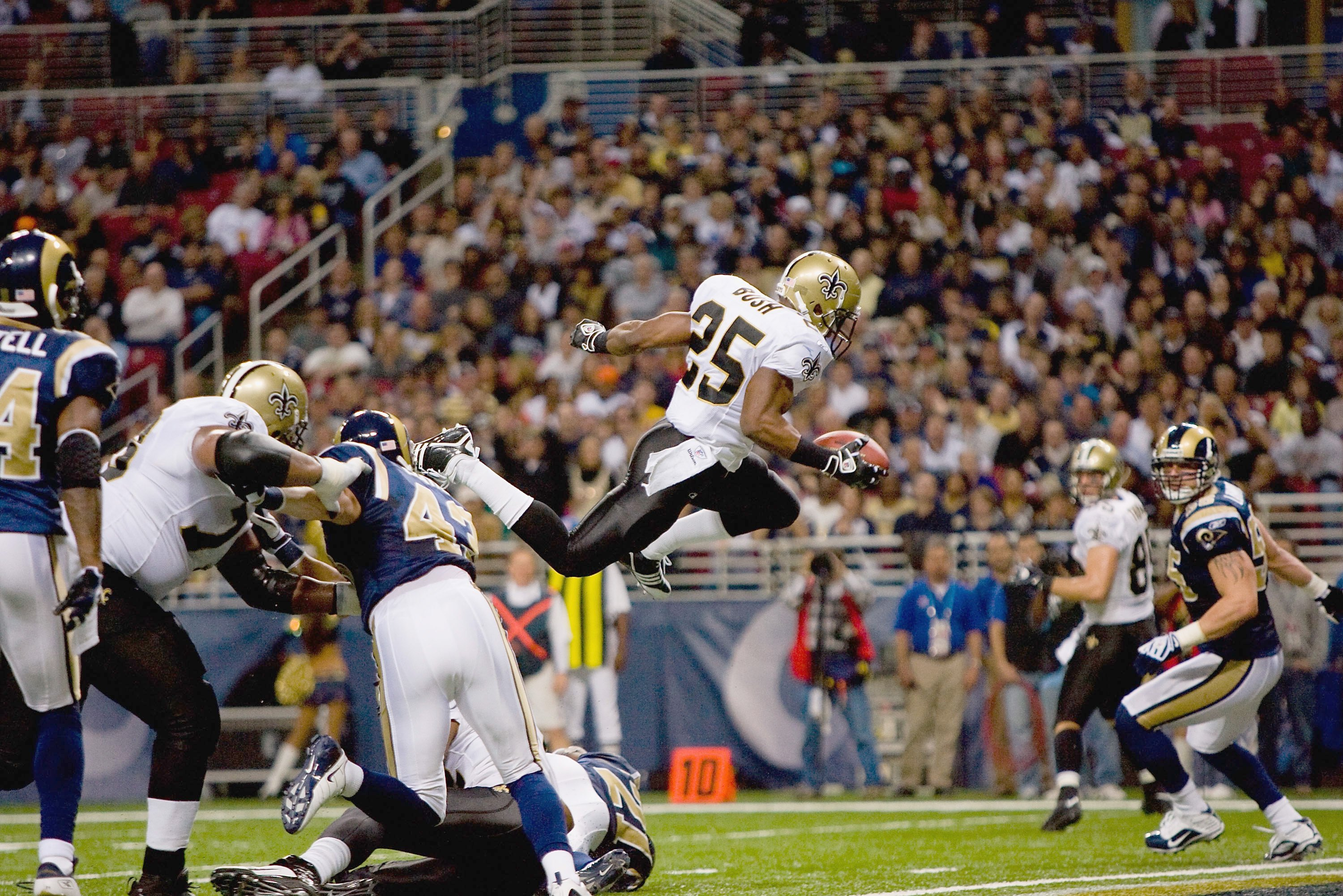 ST. LOUIS - NOVEMBER 15:  Reggie Bush #25 of the New Orleans Saints leaps for the endzone during the game against the St. Louis Rams at the Edward Jones Dome on November 15, 2009 in St. Louis, Missouri.  (Photo by Dilip Vishwanat/Getty Images)
