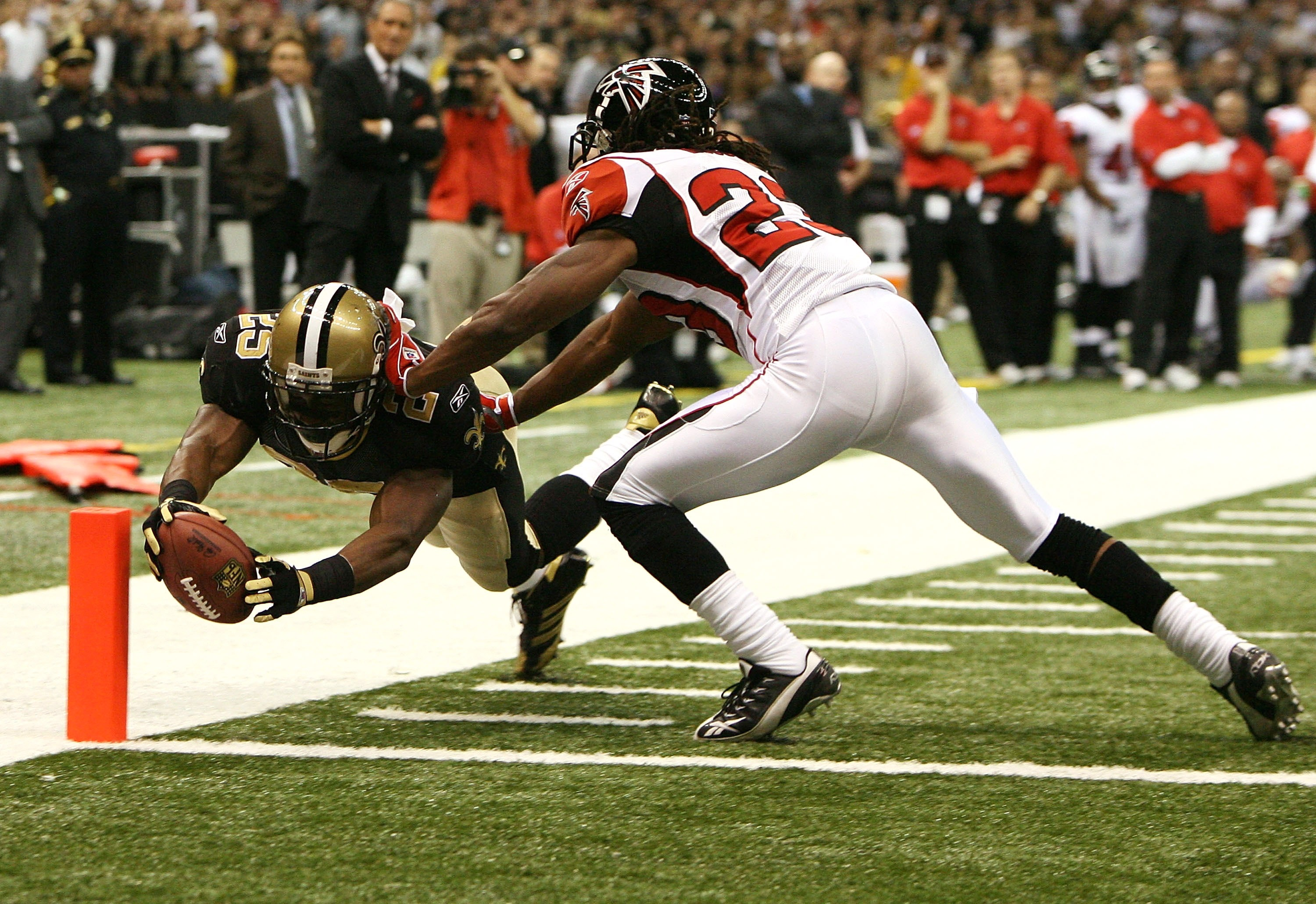 NEW ORLEANS - OCTOBER 21:  Running back Reggie Bush #25 of the New Orleans Saints dives for the pylon as he scores a two-point conversion past cornerback Chris Houston #23 of the Atlanta Falcons at the Superdome on October 21, 2007 in New Orleans, Louisia
