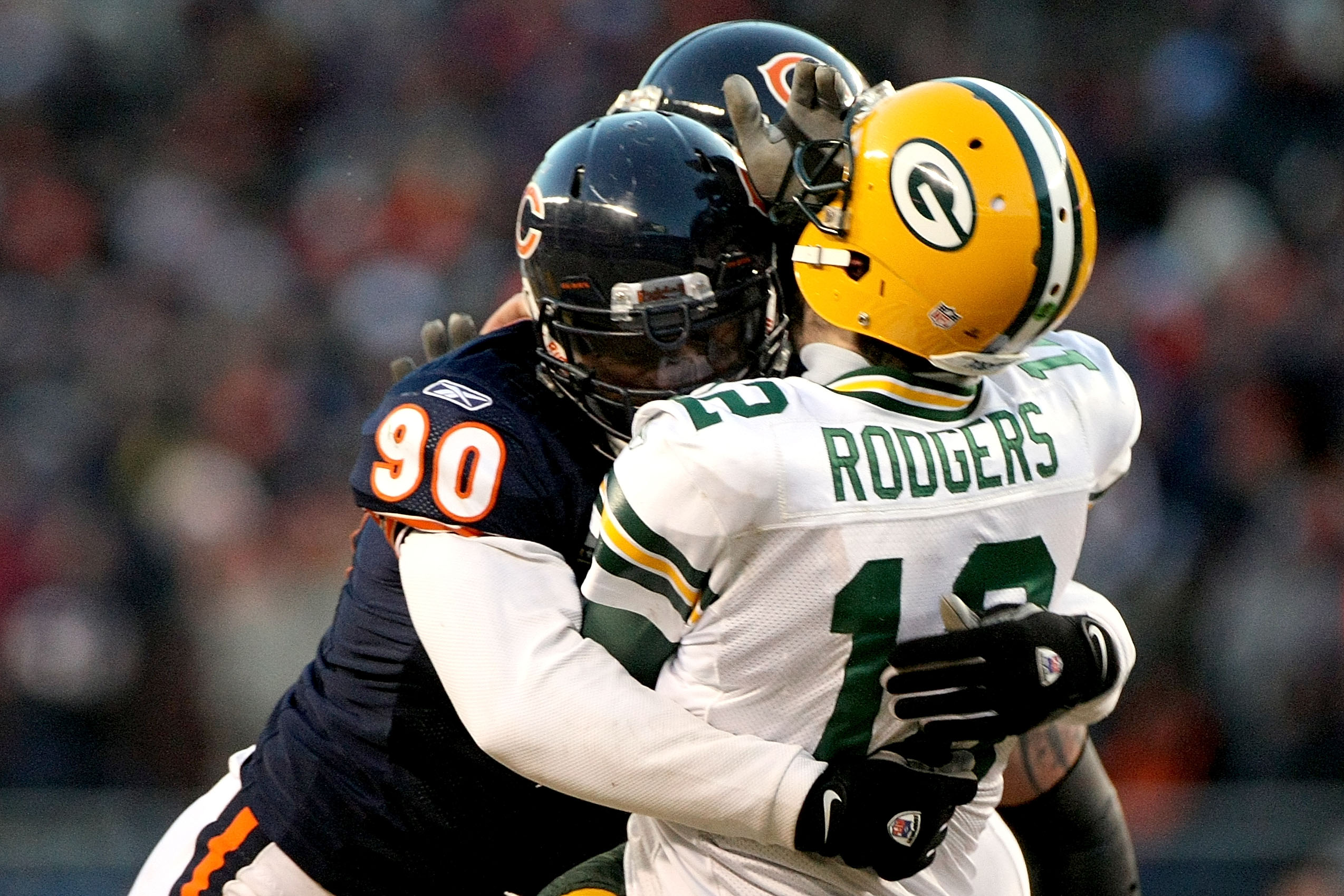 CHICAGO, IL - JANUARY 23:  Quarterback Aaron Rodgers #12 of the Green Bay Packers is hit by Julius Peppers #90 of the Chicago Bears in the helmet as Peppers was called for a personal foul in the fourth quarter of the NFC Championship Game at Soldier Field