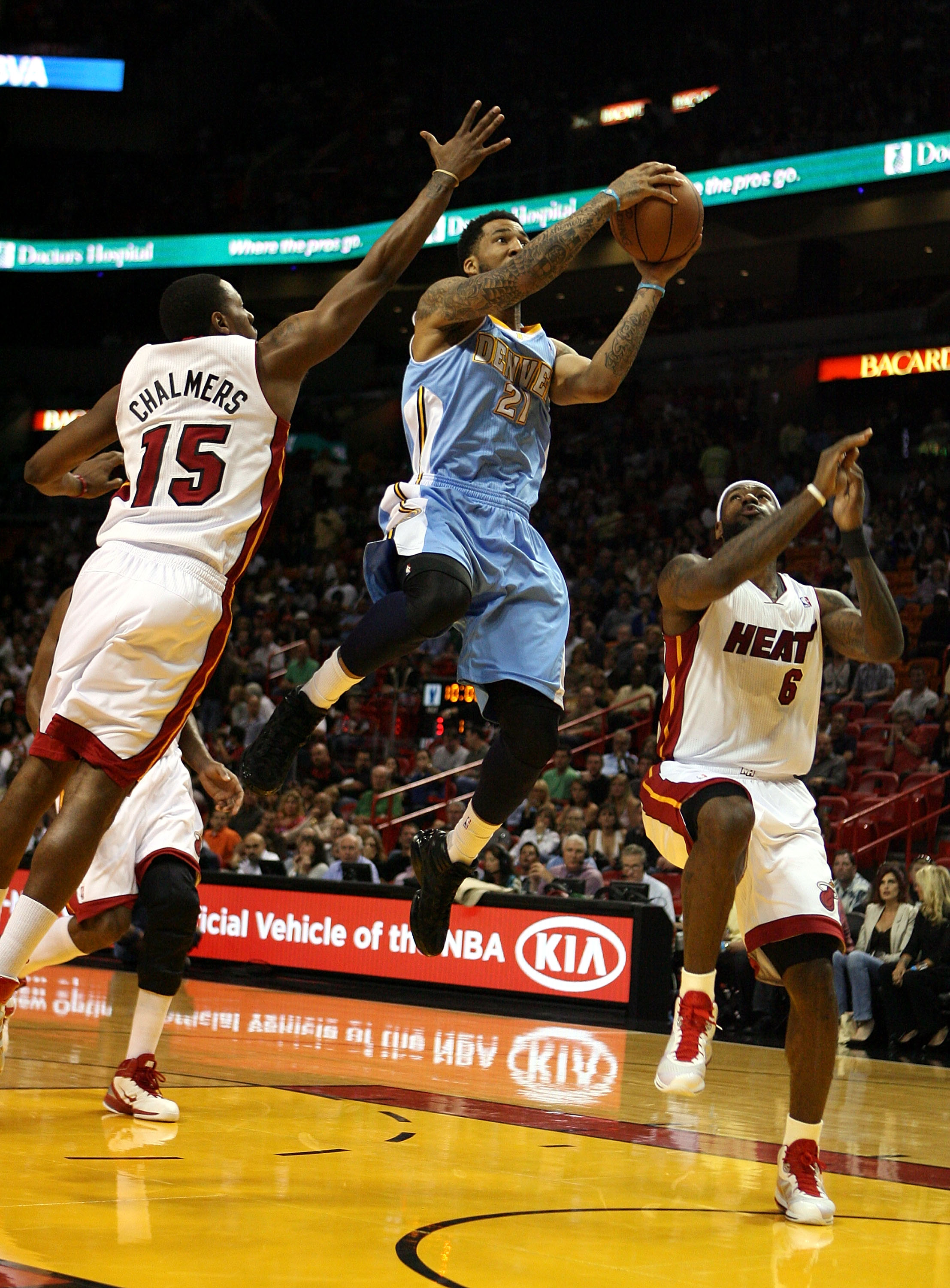 MIAMI, FL - MARCH 19:  Forward Wilson Chandler #21 of the Denver Nuggets (C) drives against Mario Chambers #15 and Dwyane Wade #3 of the Miami Heat at American Airlines Arena on March 19, 2011 in Miami, Florida.  The Heat defeated the Nuggets 103-98. NOTE