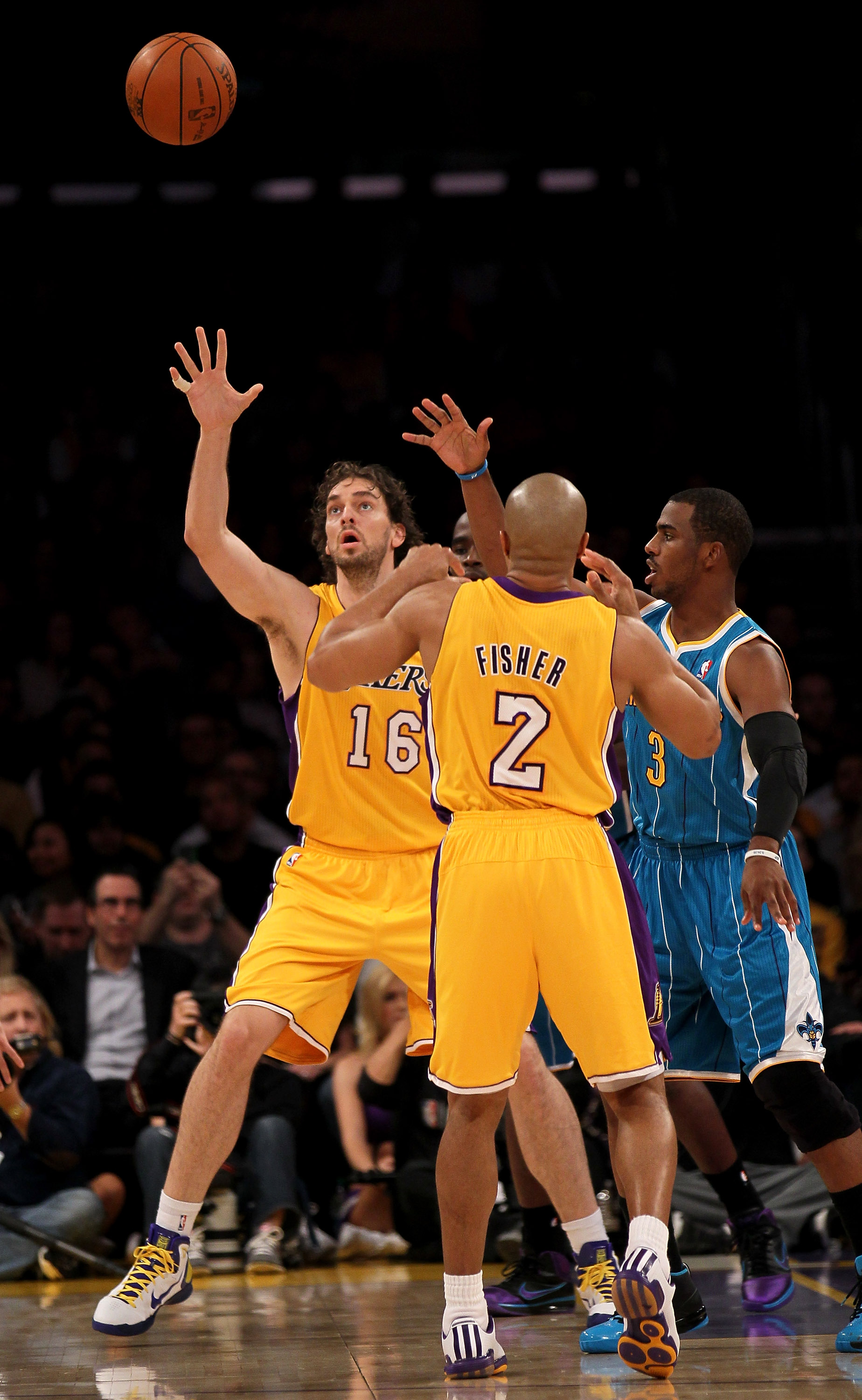 LOS ANGELES, CA - JANUARY 07:  Pau Gasol #16 of the Los Angeles Lakers reaches for a pass from Derek Fisher #16 as Chris Paul #3 of the New Orleans Hornets defends at Staples Center on January 7, 2011 in Los Angeles, California.  The Lakers won 101-97.  N