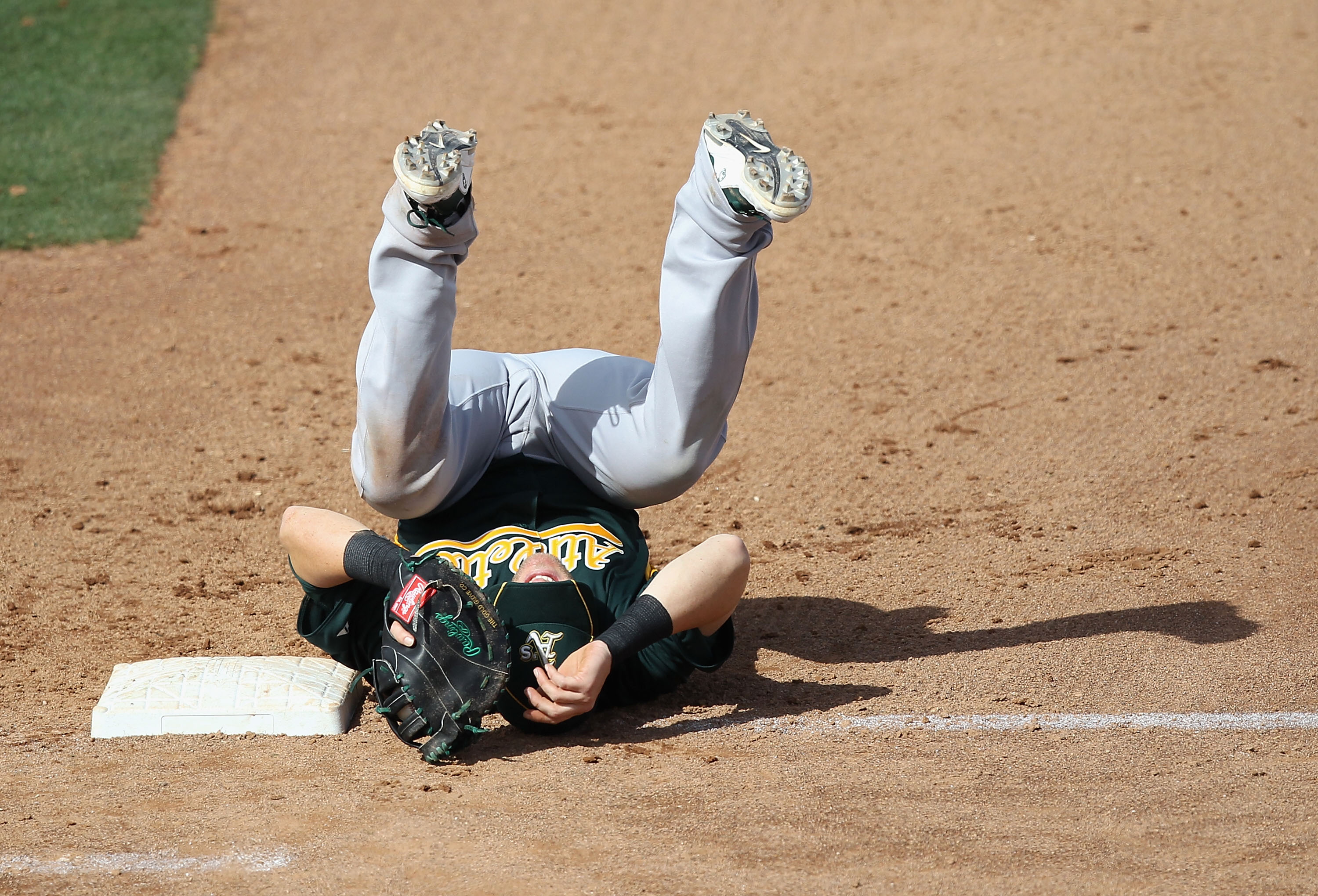 PEORIA, AZ - MARCH 06:  Infielder Daric Barton #10 of the Oakland Athletics lands on his back after a collision with Logan Forsythe (not pictured) of the San Diego Padres during the third inning of the spring training game at Peoria Stadium on March 6, 20