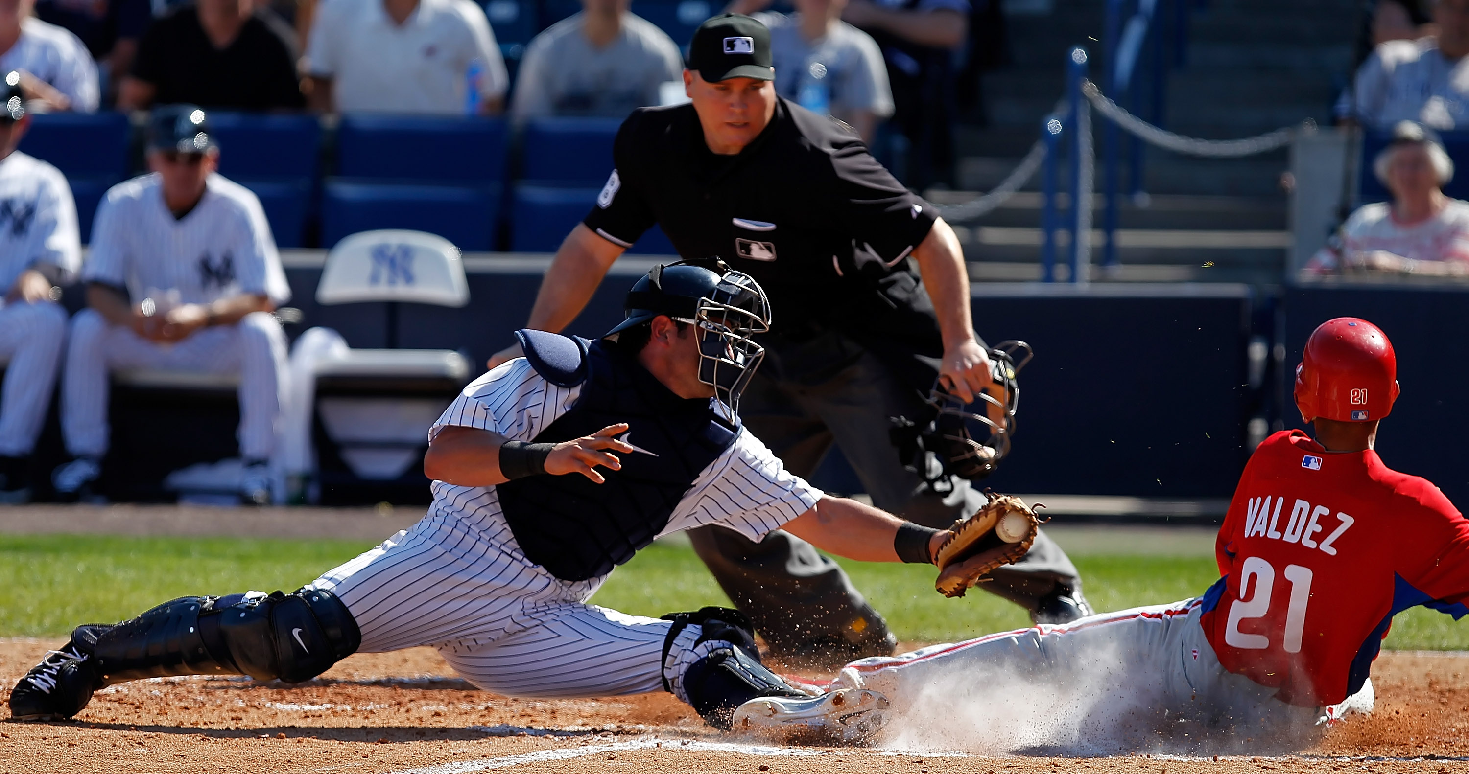 TAMPA, FL - FEBRUARY 26:  Outfielder Wilson Valdez #21 of the Philadelphia Phillies scores a run as catcher Francisco Cervelli #17 of the New York Yankees is late with the tag during a Grapefruit League Spring Training Game at George M. Steinbrenner Field