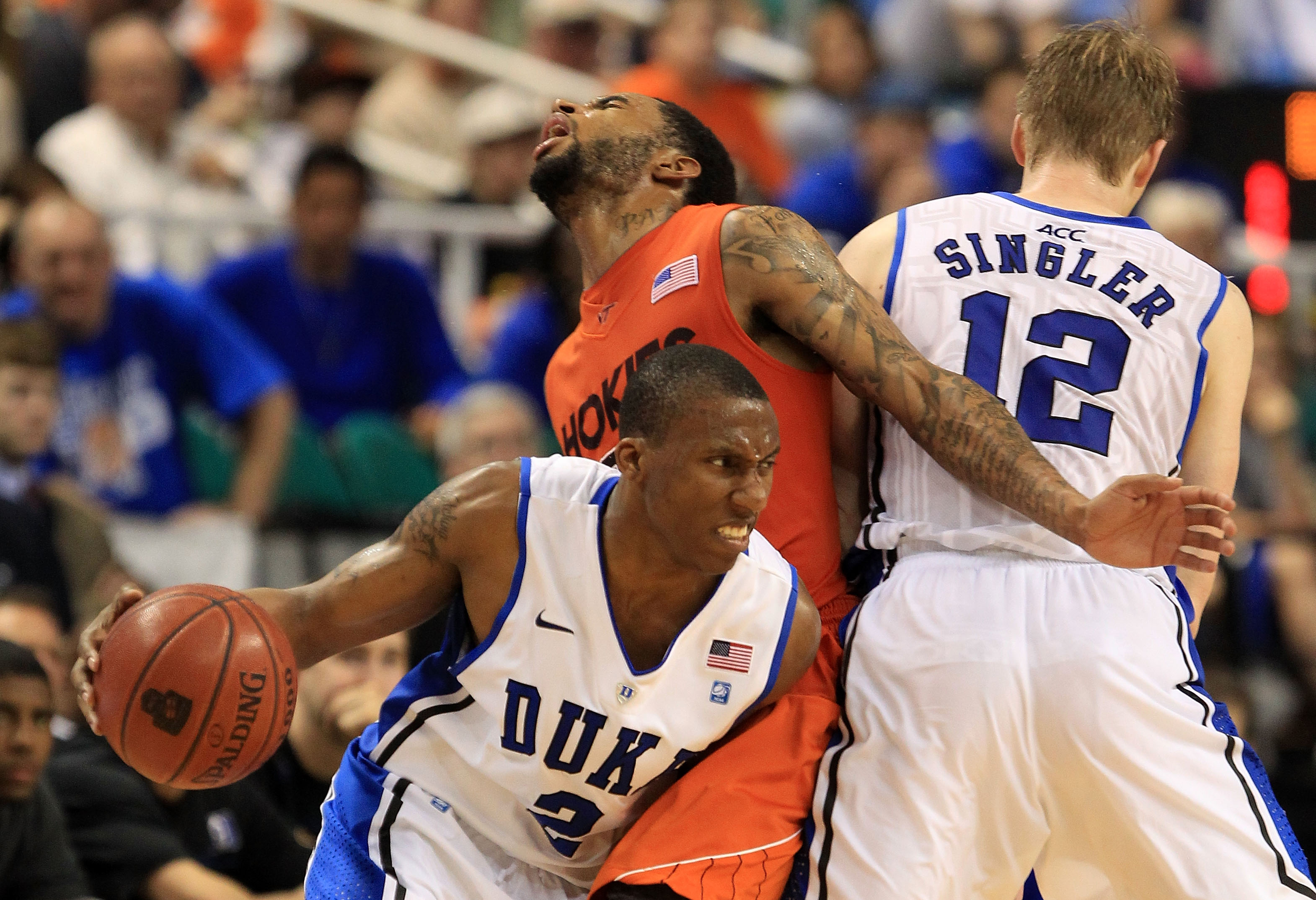 GREENSBORO, NC - MARCH 12:  Malcolm Delaney #23 of the Virginia Tech Hokies is blocked by Kyle Singler #12 of the Duke Blue Devils as teammate Nolan Smith #2 drives the ball during the second half in the semifinals of the 2011 ACC men's basketball tournam
