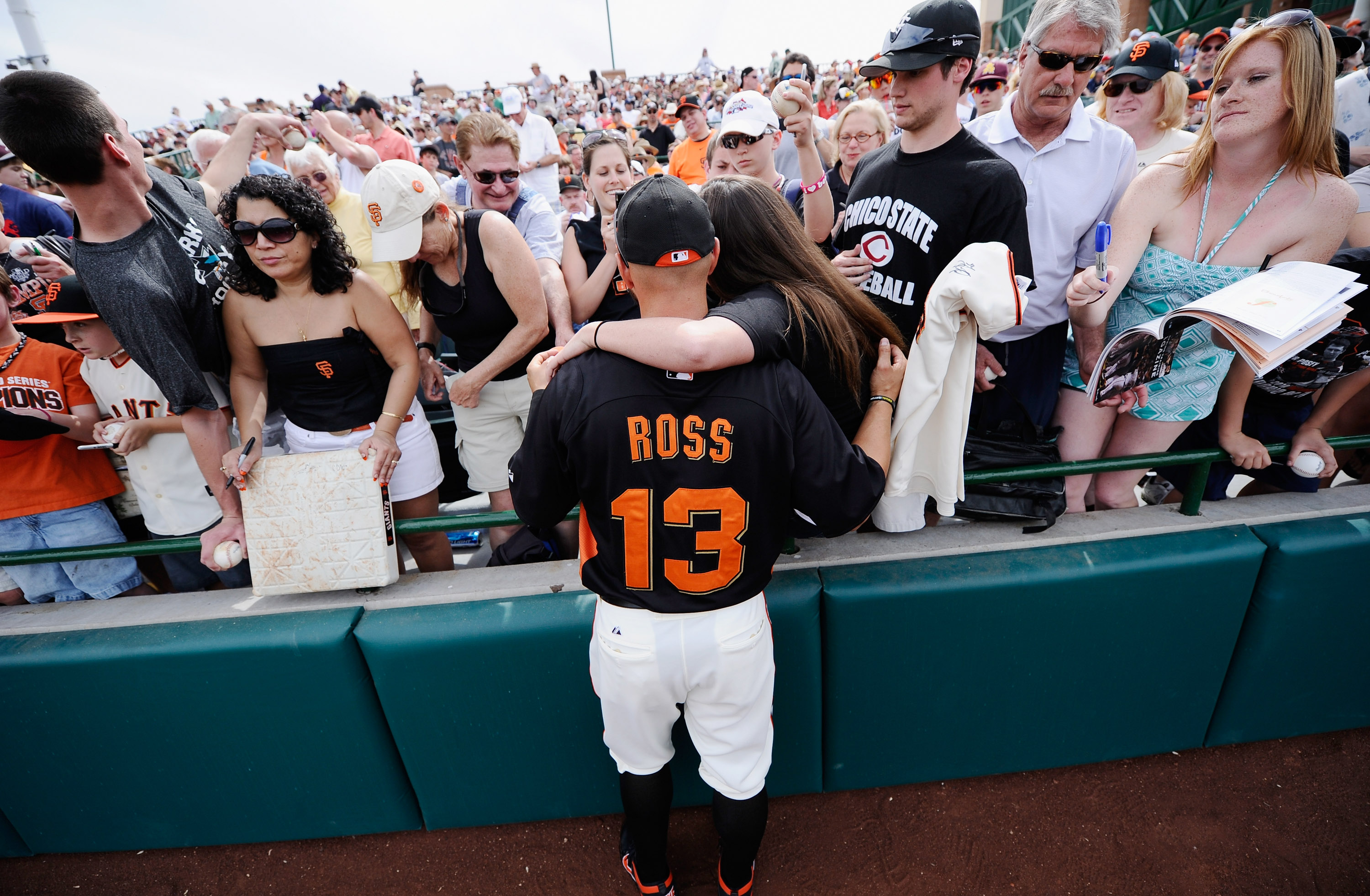 SCOTTSDALE, AZ - MARCH 14:  Cody Ross #13 of the San Francisco Giants gets his picture taken with fans priror to the start of the spring training baseball game against Milwaukee Brewers at Scottsdale Stadium on March 14, 2011 in Scottsdale, Arizona.  (Pho