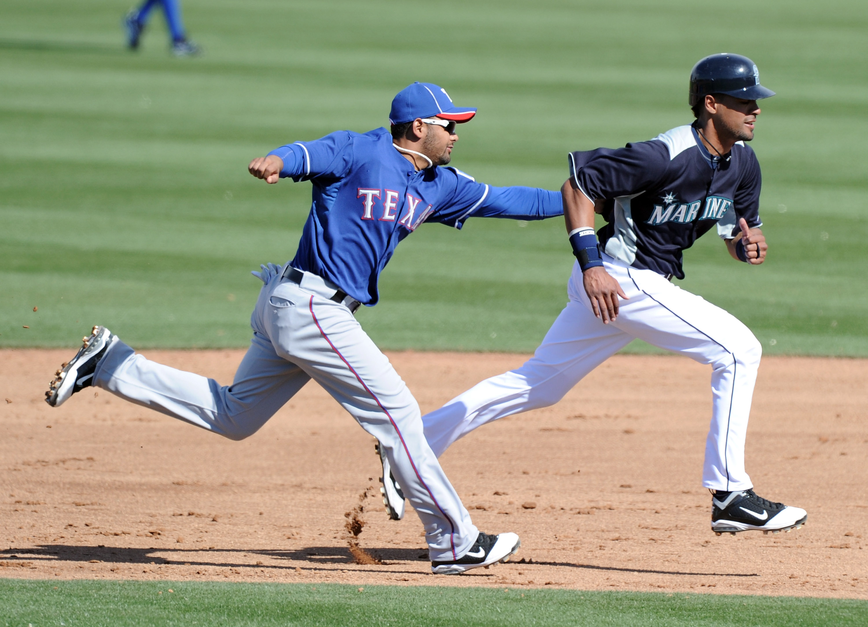 PEORIA, AZ - MARCH 01:  Andres Blanco #3 of the Texas Rangers tags Franklin Gutierrez #21 of the Seattle Mariners for an out during an attempted steal in the sixth inning during spring training at Peoria Stadium on March 1, 2011 in Peoria, Arizona.  (Phot