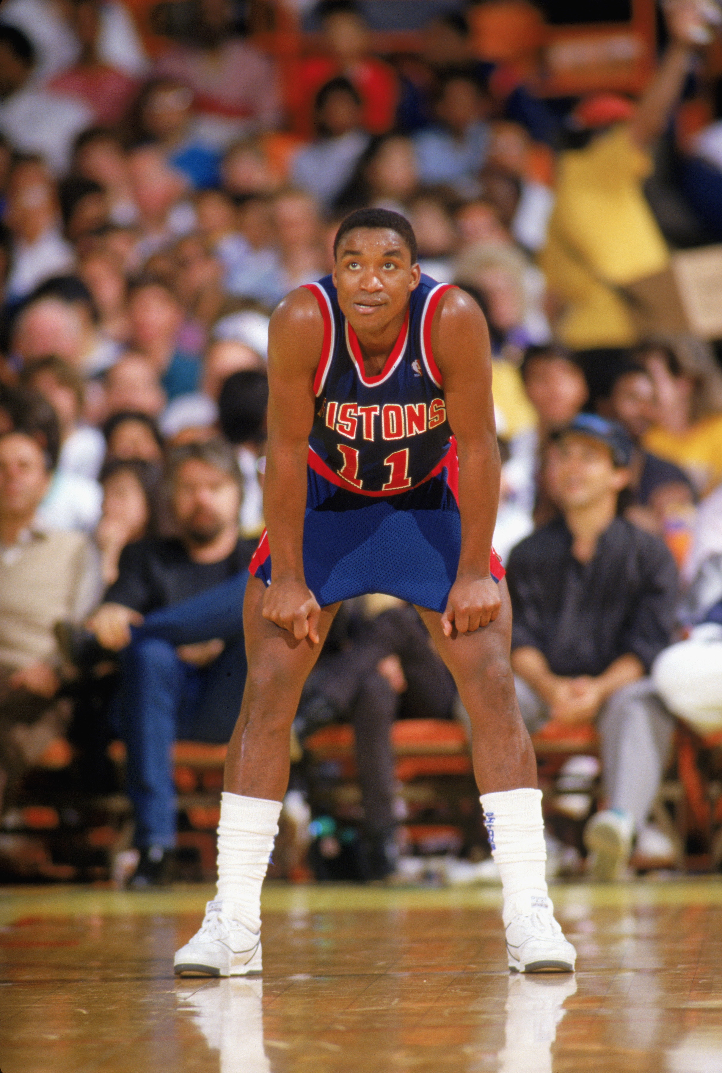 1987:  Isiah Thomas #11 of the Detroit Pistons looks on as he waits for play during a game in the 1987-1988 NBA season.  (Photo by Rick Stewart/Getty Images)
